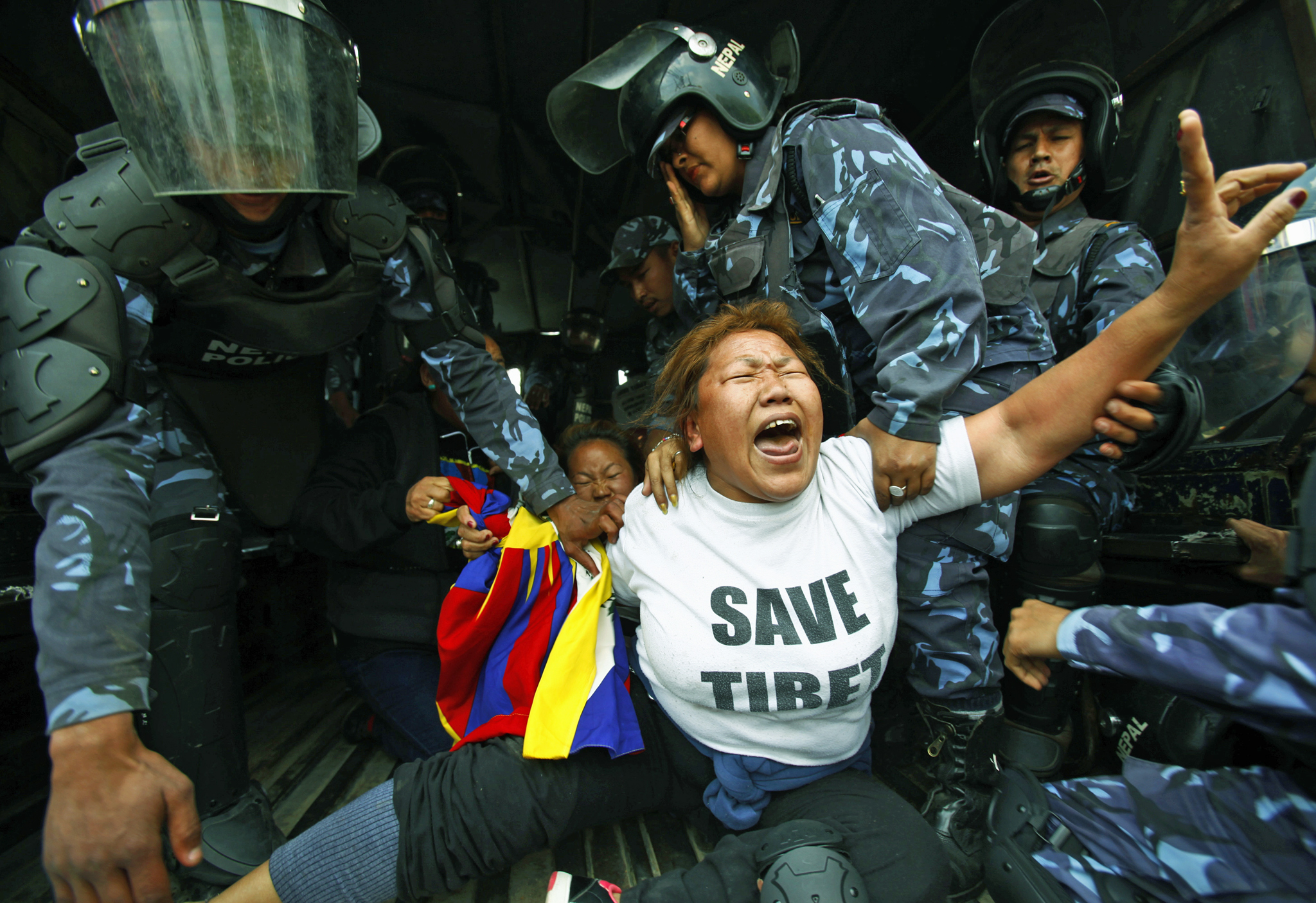Nepalese policemen detain exiled Tibetans as they shout slogans during a protest outside the Chinese embassy visa office in Katmandu, Nepal, Monday, March 10, 2014. Police broke up a small Tibetan protest in Nepal's capital and detained the protesters on Monday's anniversary of a failed 1959 uprising against Chinese rule in Tibet. Tibetan refugees in Nepal regularly demonstrate against Chinese rule over their homeland.