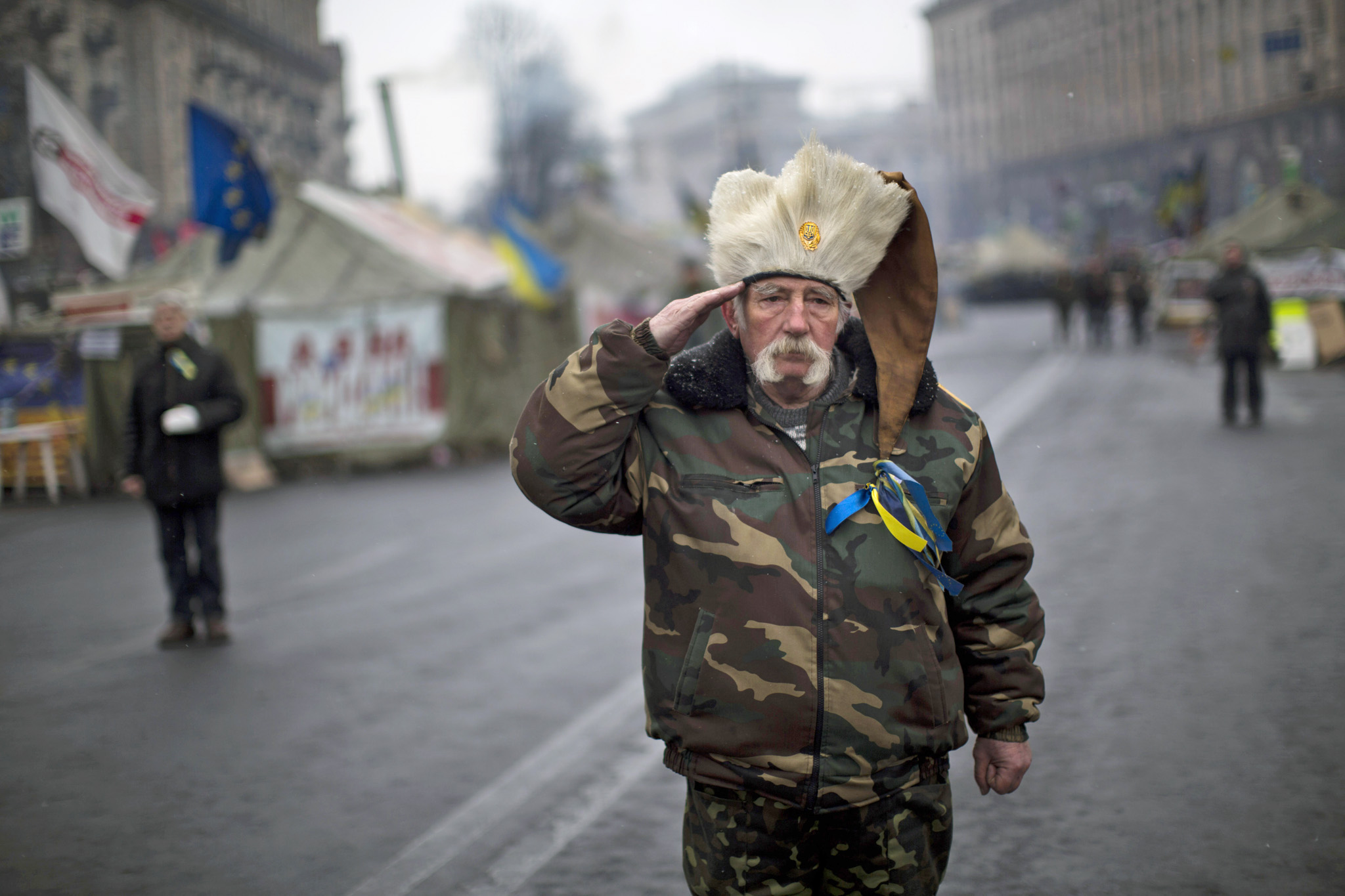An anti-Yanukovych protester salutes as the Ukrainian national anthem is played at Kiev's Independence Square, Ukraine, Monday, March 3, 2014. The U.S. and its allies are weighing sanctions on Moscow and whether to bolster defenses in Europe in response to Russia's military advances on Ukraine.