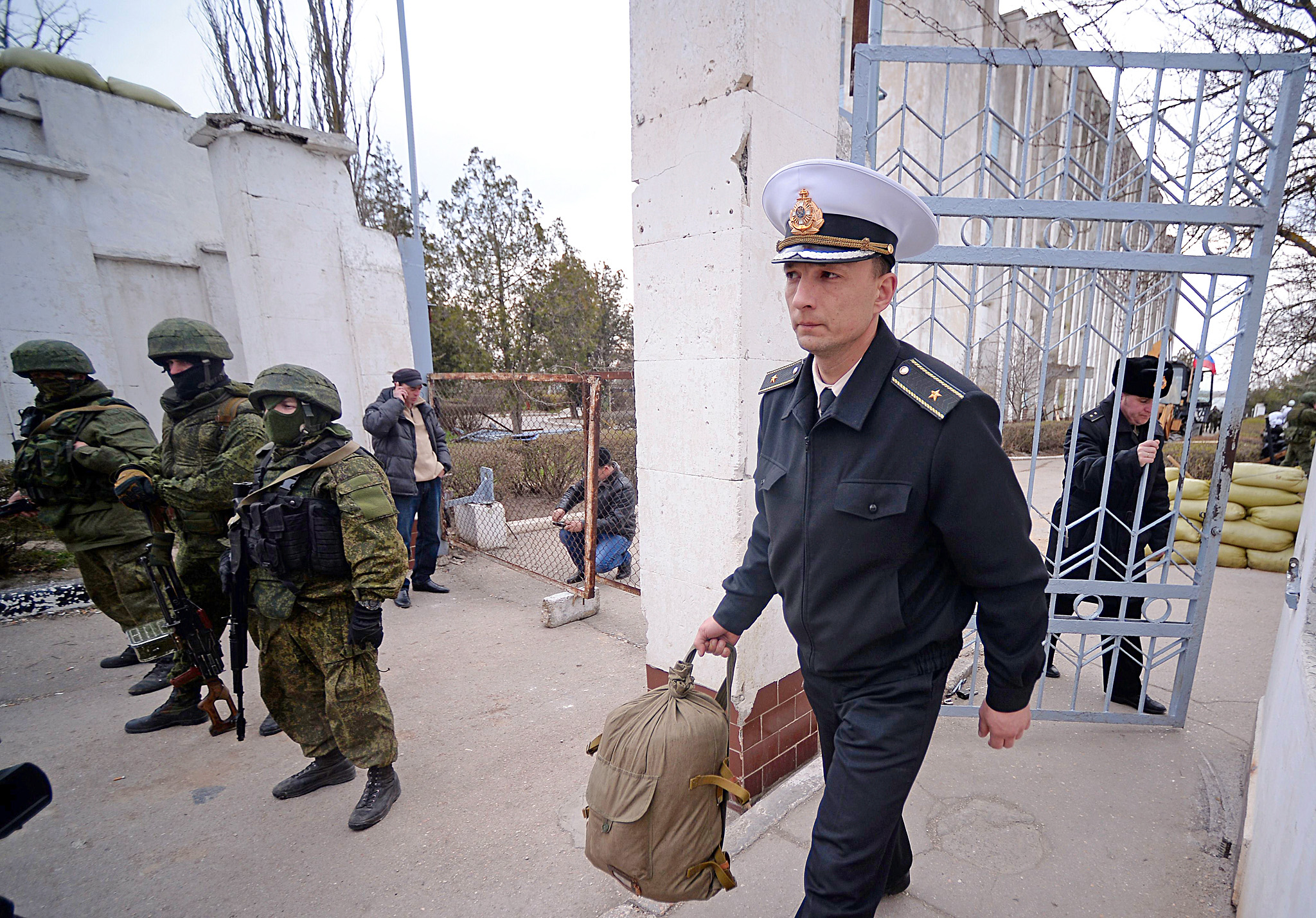 A Ukrainian officer leaves as Russian so...A Ukrainian officer leaves as Russian soldiers stand guard after they took control of the Ukrainian navy south headquarters base in Novoozerne on March 19, 2014. Russian forces seized control of a second Ukrainian navy base in western Crimea on March 19, hours after capturing the main navy headquarters in Sevastopol. Some 50 Ukrainian servicemen were seen filing out of the base at Novoozerne as Russian soldiers stood by, while pro-Moscow militants raised the Russian flag over the base.  AFP PHOTO/ Filippo MONTEFORTE FILIPPO MONTEFORTE/AFP/Getty Images