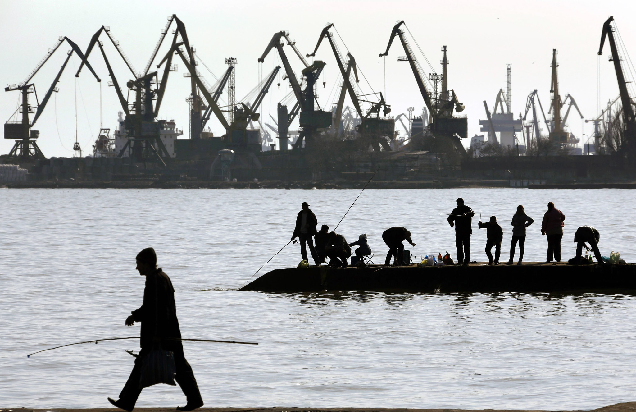 People fish on a pier at the port of Mariupol...People fish on a pier at the port of Mariupol, located on the north of the Sea of Azov in eastern Ukraine March 26, 2014. REUTERS/Yannis Behrakis