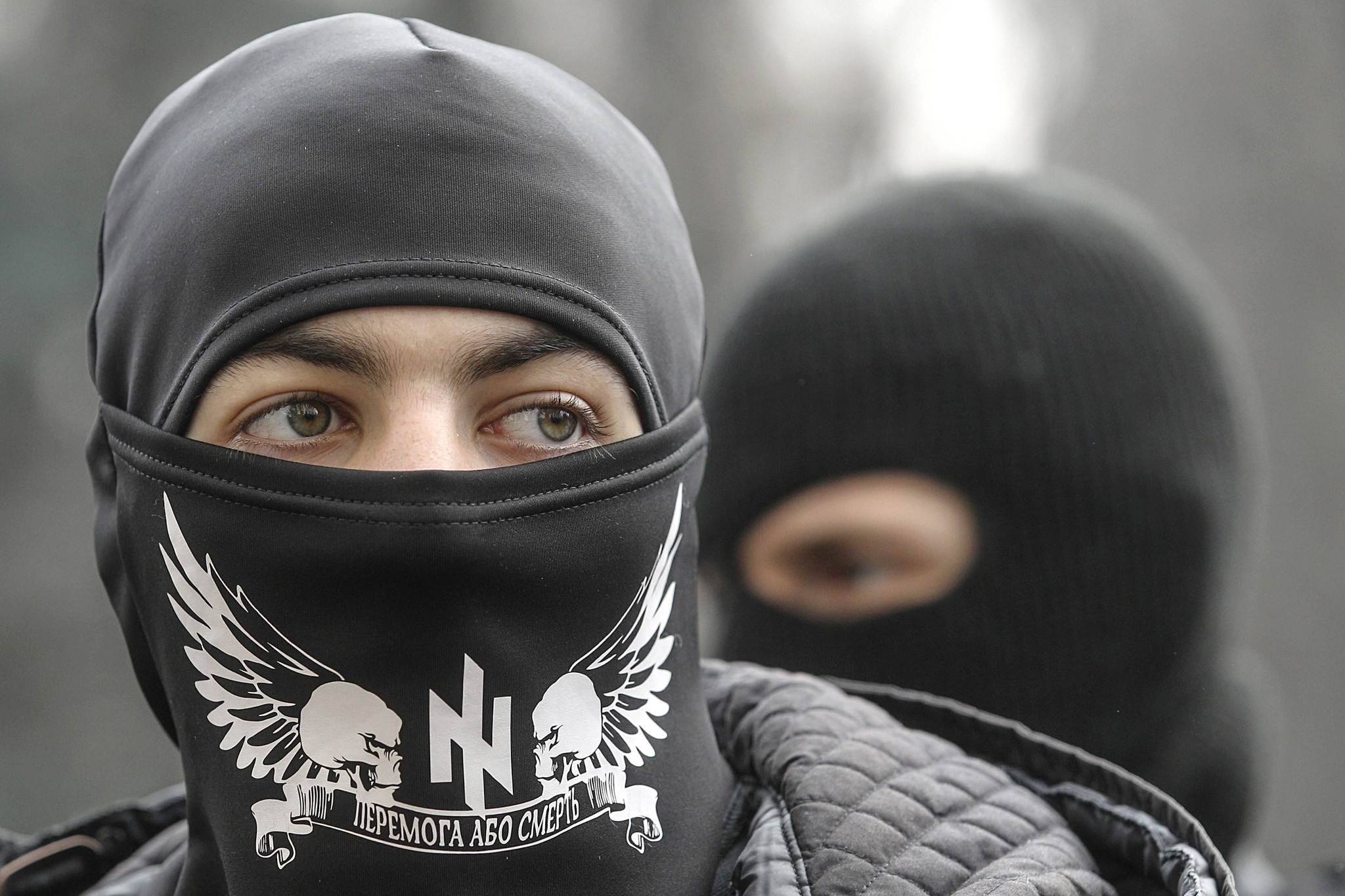 "Members of the Ukrainian far-right radical group Right Sector stand outside the parliament in Kiev...Members of the Ukrainian far-right radical group Right Sector stand outside the parliament in Kiev March 28, 2014. Ukrainian authorities carried out an inspection tour of Kiev's bomb shelters on Friday as lawmakers accused Russia of fomenting trouble in the Ukrainian capital after having annexed the Black Sea region of Crimea. The slogan on the face mask reads ""Victory or death"". REUTERS/Valentyn Ogirenko"
