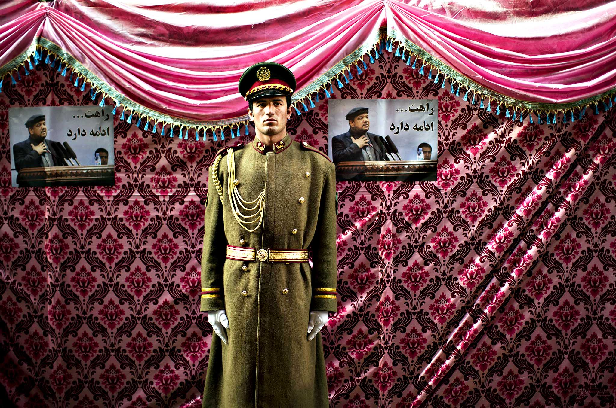 An Afghan honour  guard stands next to pictures of late Afghan Vice President Field Marshal Mohammed Qasim Fahim outside his house in Kabul, Afghanistan, Monday, March 10, 2014. Afghanistan's influential Vice President Fahim, a leading commander in the alliance that fought the Taliban who was later accused with other warlords of targeting civilian areas during the country's civil war, died on Sunday. He was 57.