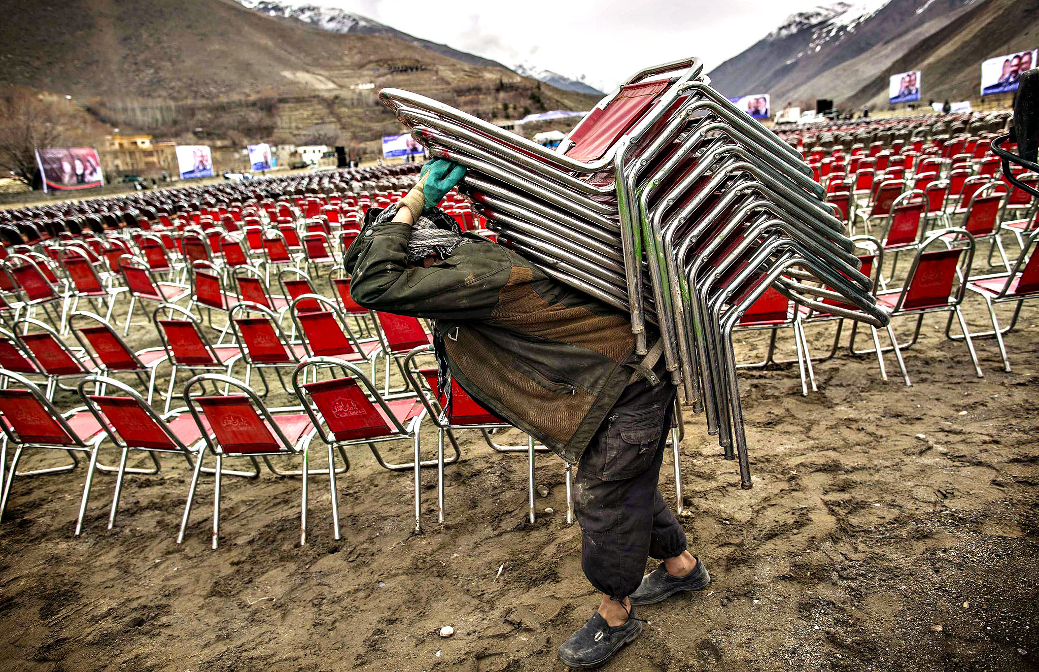 A supporter of Afghan presidential candidate Zalmai Rassoul carries chairs as he prepares for an election rally in Panshir, northern Afghanistan, March 28, 2014. Afghan presidential elections will be held on April 5.