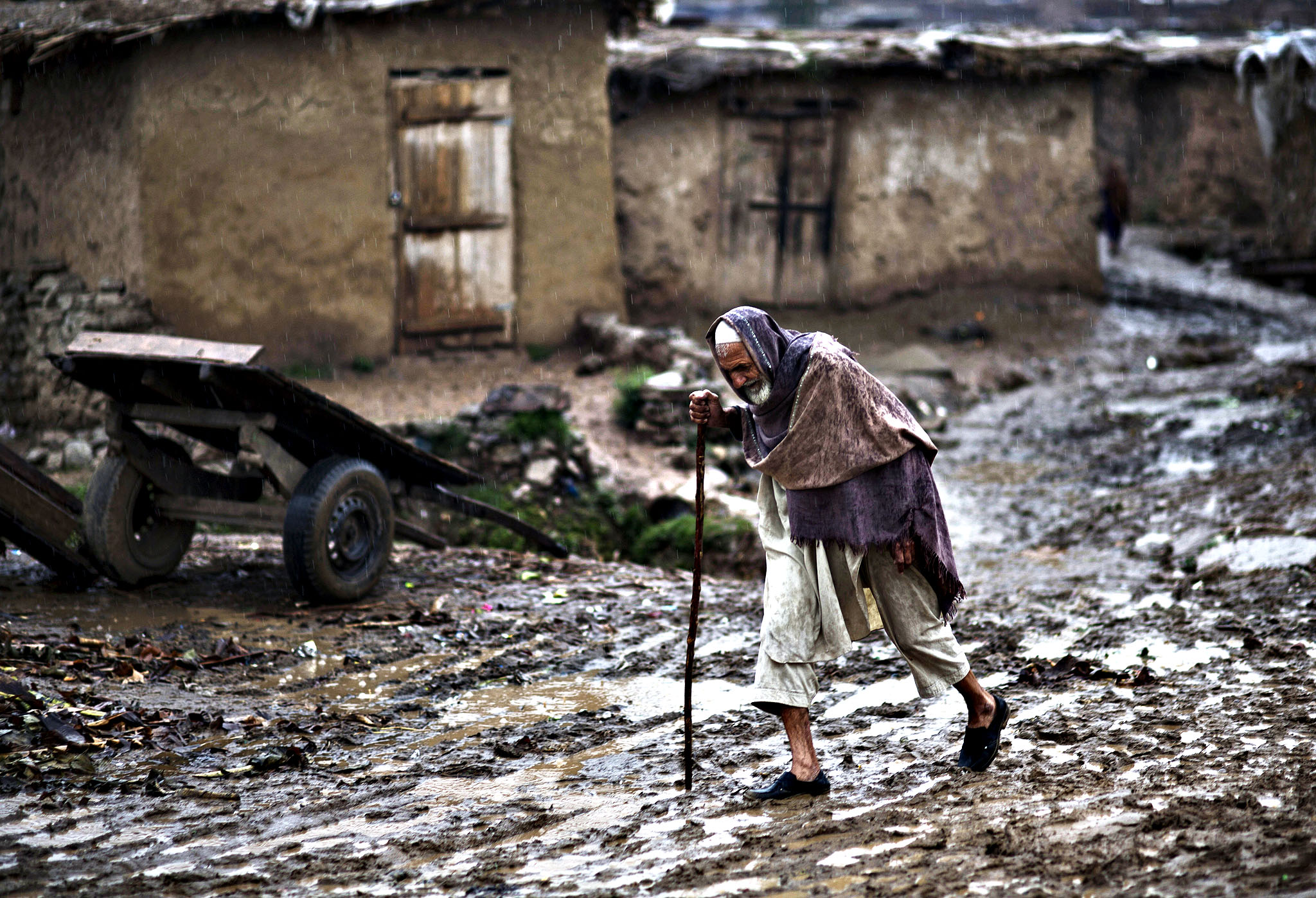 An elderly Afghan refugee man walks toward the main road through a muddy slippery track, during a rainfall in a poor neighborhood on the outskirts of Islamabad, Pakistan, Friday, March 28, 2014. For more than three decades, Pakistan has been home to one of the world s largest refugee communities: hundreds of thousands of Afghans who have fled the repeated wars and fighting in their country. Since the 2002 U.S.-led invasion of Afghanistan some 3.8 million Afghans have returned to their home country, according to the U.N. s refugee agency, thousands of them still live without electricity, running water and other basic services.