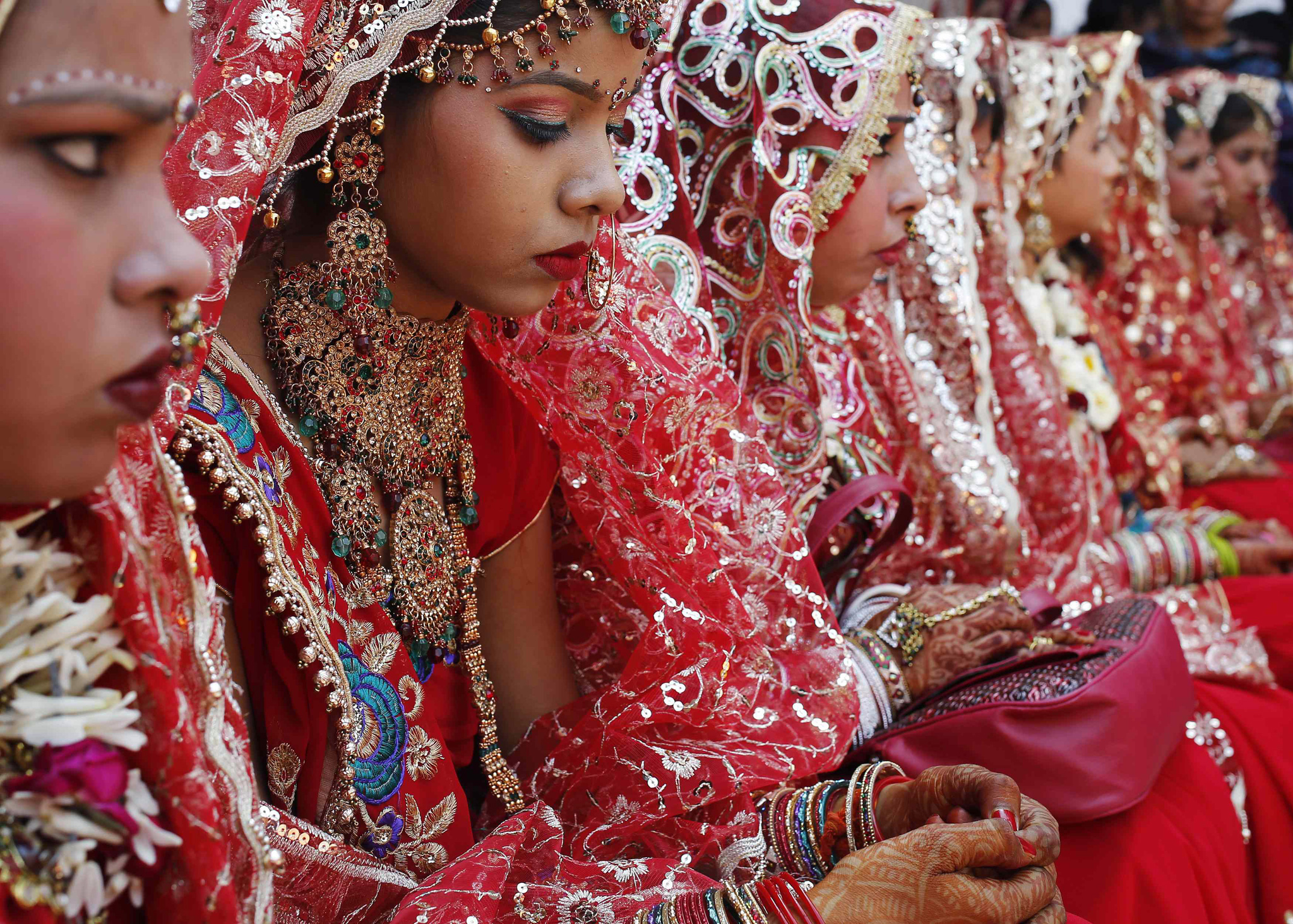 Brides sit as they wait to take their wedding vows during a mass wedding ceremony at a temple in New Delhi...Brides sit as they wait to take their wedding vows during a mass wedding ceremony at a temple in New Delhi March 3, 3014. A total of 11 couples exchanged wedding vows on Monday during the mass wedding ceremony arranged by a Hindu voluntary organisation, organisers said. REUTERS/Anindito Mukherjee