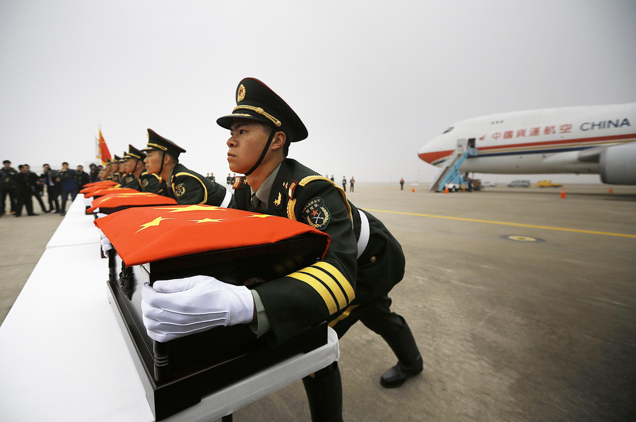 Chinese honour guards lift caskets containing the remains of Chinese soldiers during the handing over ceremony of the remains at the Incheon International Airport in Incheon