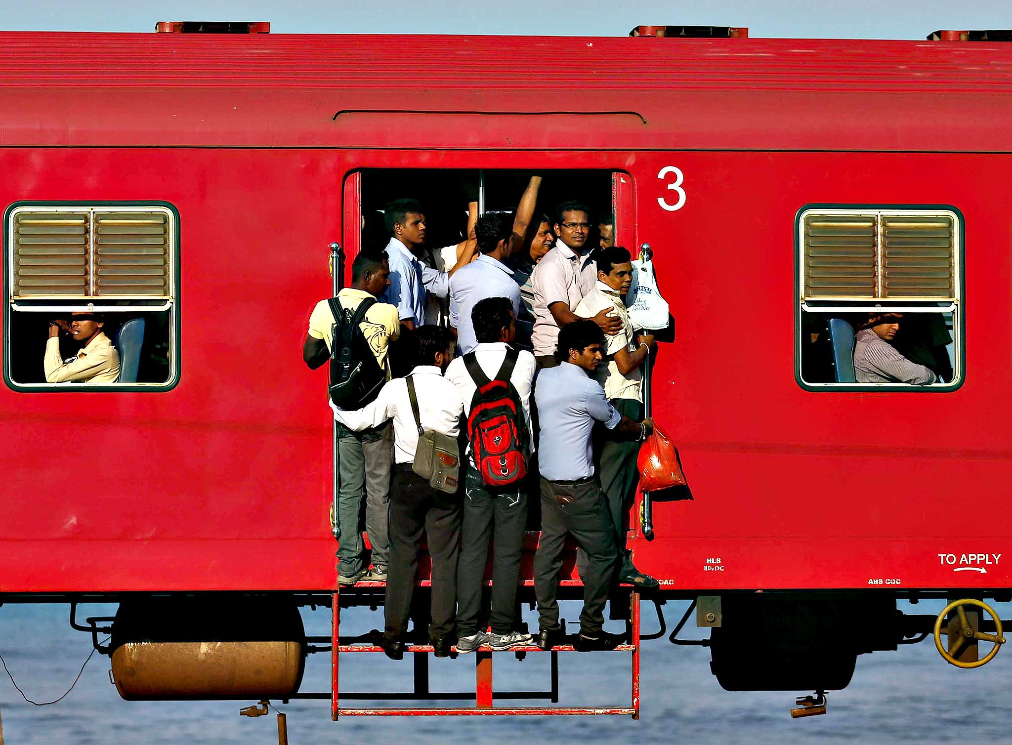 People hang onto a crowded local passenger train as they travel to Colombo.
