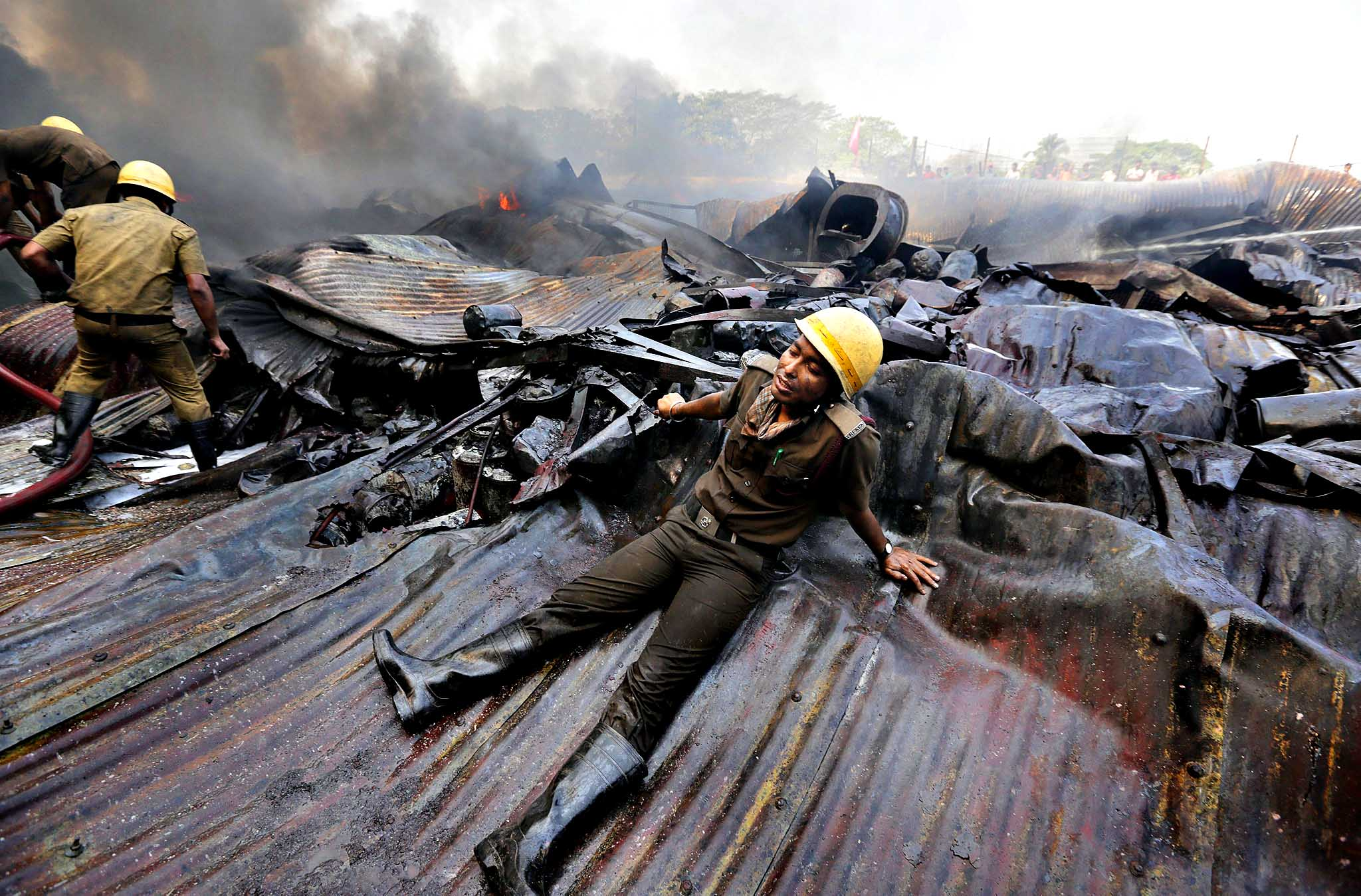 An exhausted firefighter rests on debris as they battle to extinguish a huge fire in a paint factory in Howrah, 30 km west of Calcutta, Eastern India, 12 March 2014. A major fire broke out at a factory of Shalimar Paints Limited in Howrah early morning. According to police and media reports, 25 fire engines fought for close to six hours to extinguish the blaze. Noboby was injured.