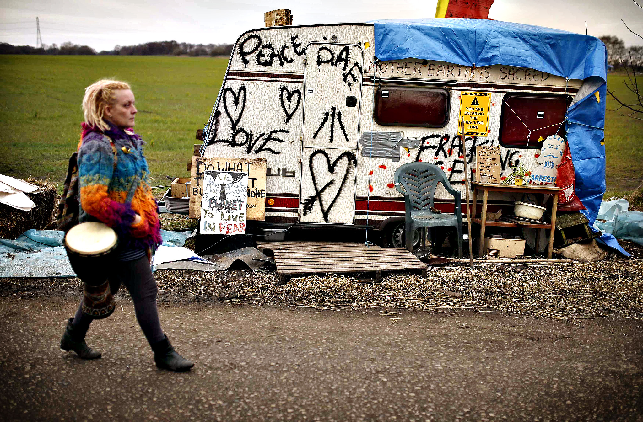 A woman walks past a graffiti covered caravan at a protest camp set up close to the entrance of the IGas exploratory gas drilling site at Barton Moss, near Manchester...A woman walks past a graffiti covered caravan at a protest camp set up close to the entrance of the IGas exploratory gas drilling site at Barton Moss, near Manchester, northern England, March 6, 2014. Britain may be a prime location for shale gas exploration in Europe, but a lack of onshore drilling infrastructure and local opposition will impede development, experts and geologists said at a shale conference in London.