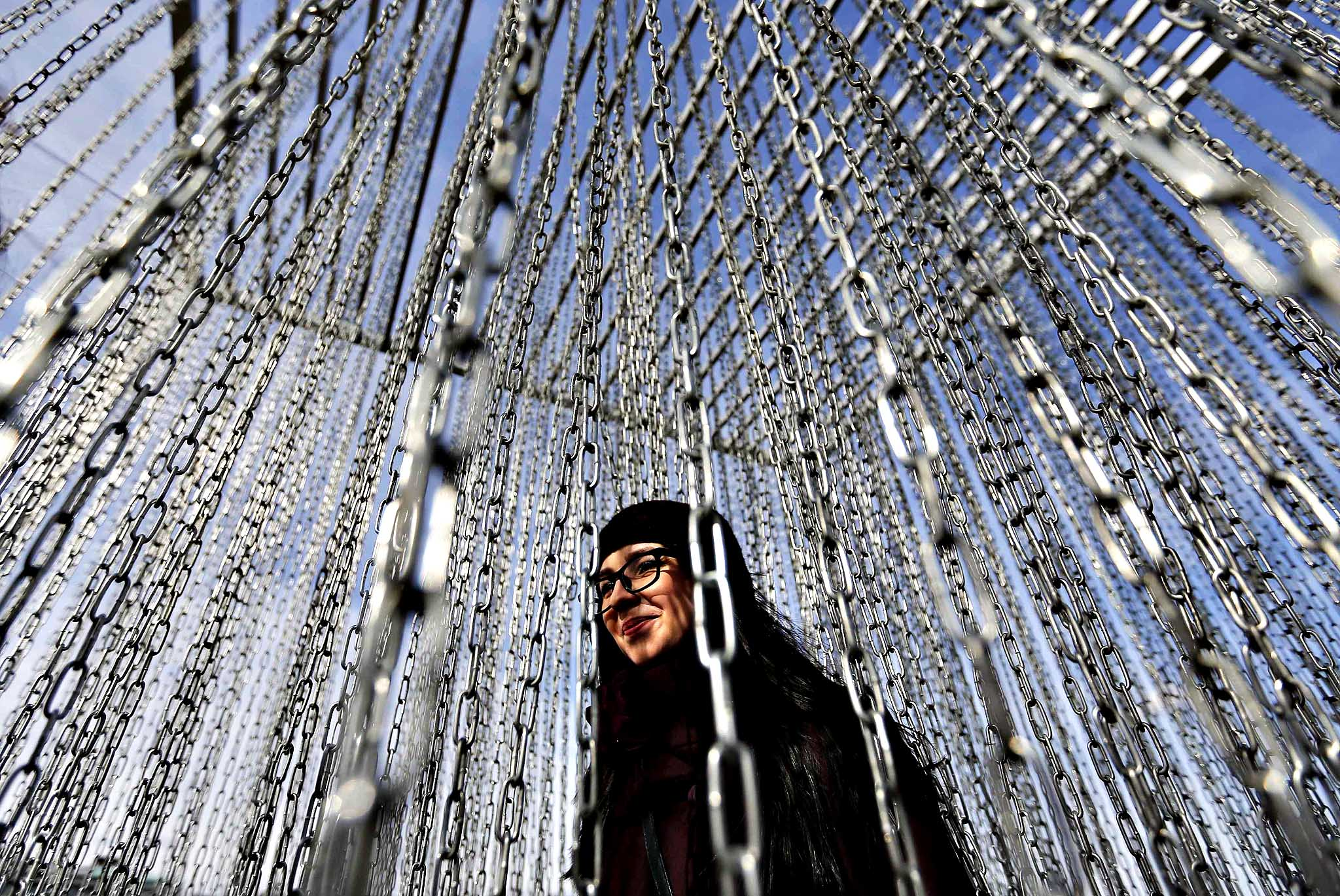 A woman walks amidst chains as she views an art installation near the Gorky Central Park of Culture and Leisure in Moscow, March 14, 2014.