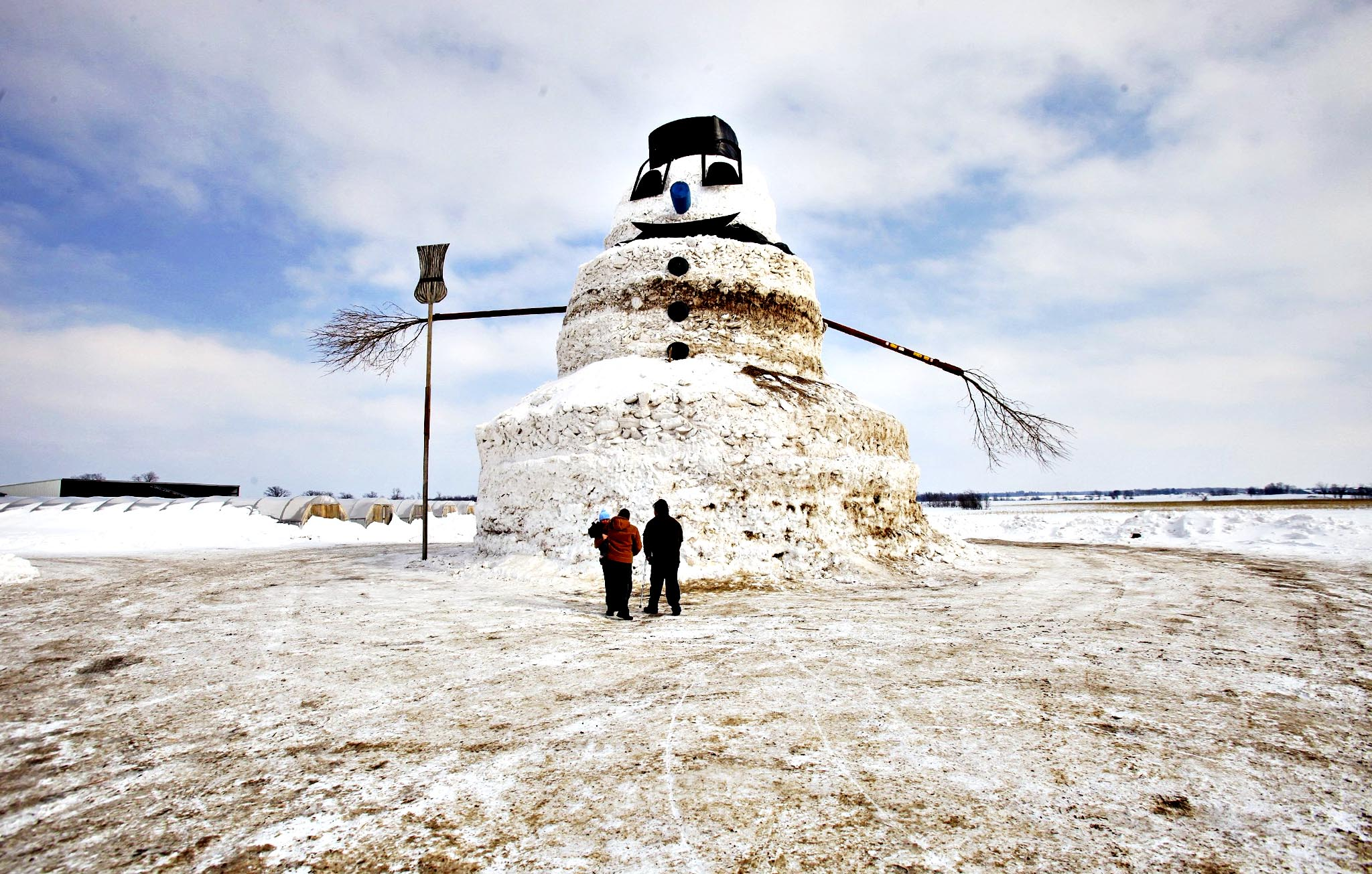 """A couple and a child look at a 50-foot snowman named """"Granddaddy"""" in Gilman, Minnesota. The snowman began to take shape earlier this winter when farmer Greg Novak needed to move mounting snow piles away from his greenhouses."""