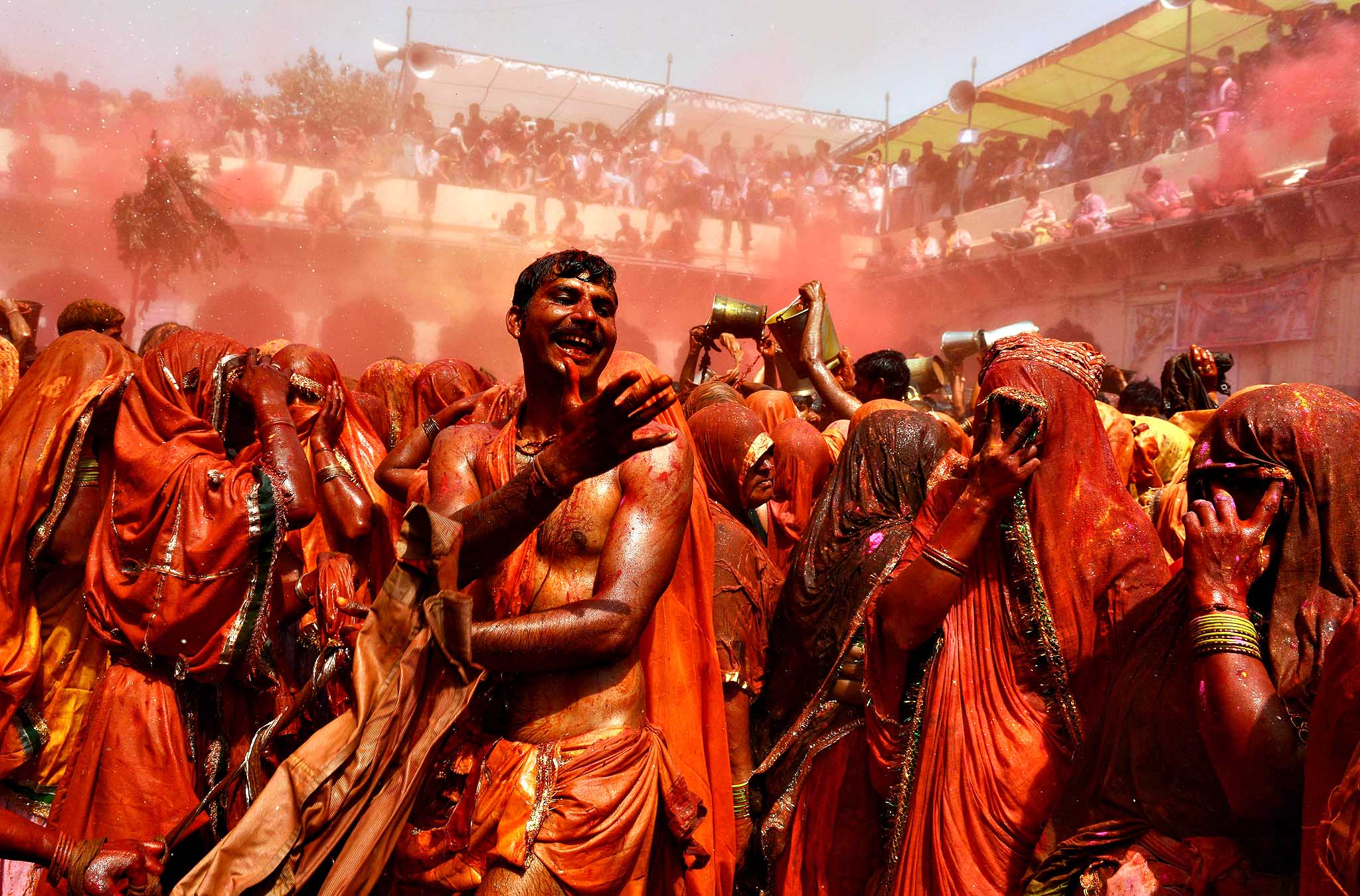 Indian revellers take part in the game of 'Huranga' at The Dauji Temple in Mathura, some 100kms south of New Delhi on March 18, 2014. 'Huranga' is a game played between men and women a day after Holi, the festival of colours, during which men drench women with liquid colours and women tear off the clothes of the men.