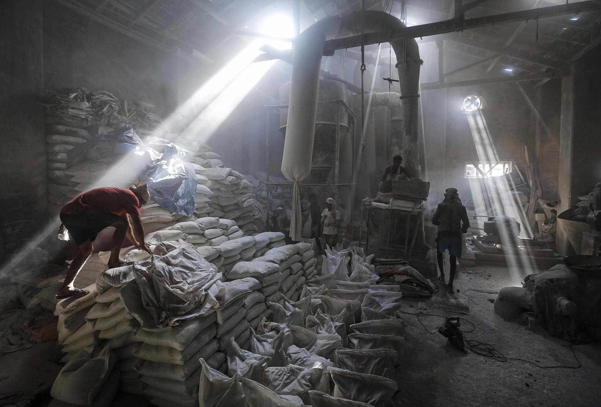 Employees work inside a limestone powder factory in an industrial area in Mumbai
