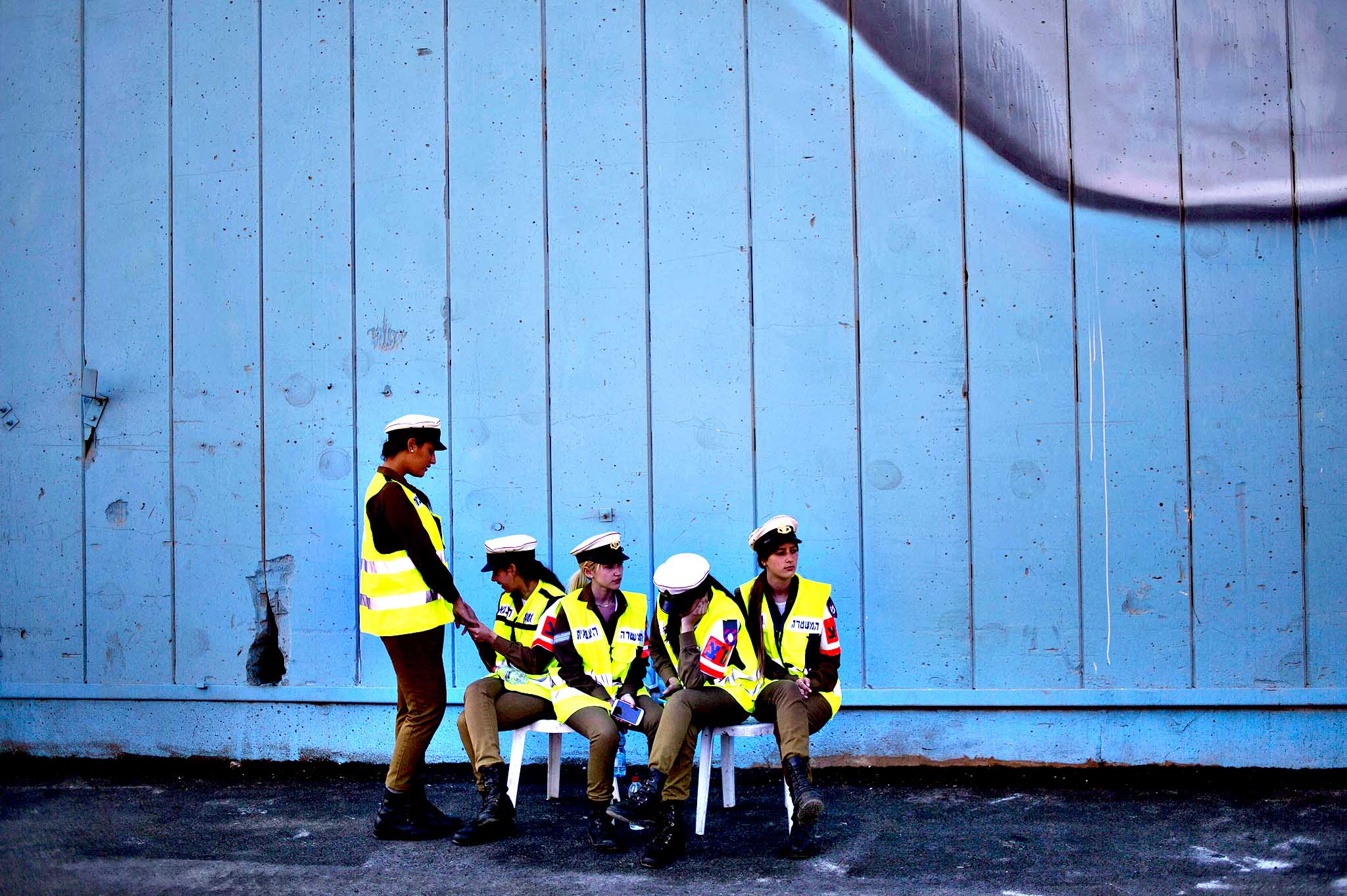 Israeli military policewomen wait for the display of rockets after being seized from the Panama-flagged KLOS C civilian cargo ship that Israel intercepted last Wednesday off the coast of Sudan, at a military port in the Red Sea city of Eilat, southern Israel, Monday, March 10, 2014. Israel has alleged the shipment was orchestrated by Iran and was intended for Islamic militants in Gaza, a claim denied by Iran and the rockets' purported recipients. Questions remain, including how the rockets would have been smuggled into Gaza, largely cut off from the world by a border blockade enforced by Israel and Egypt.
