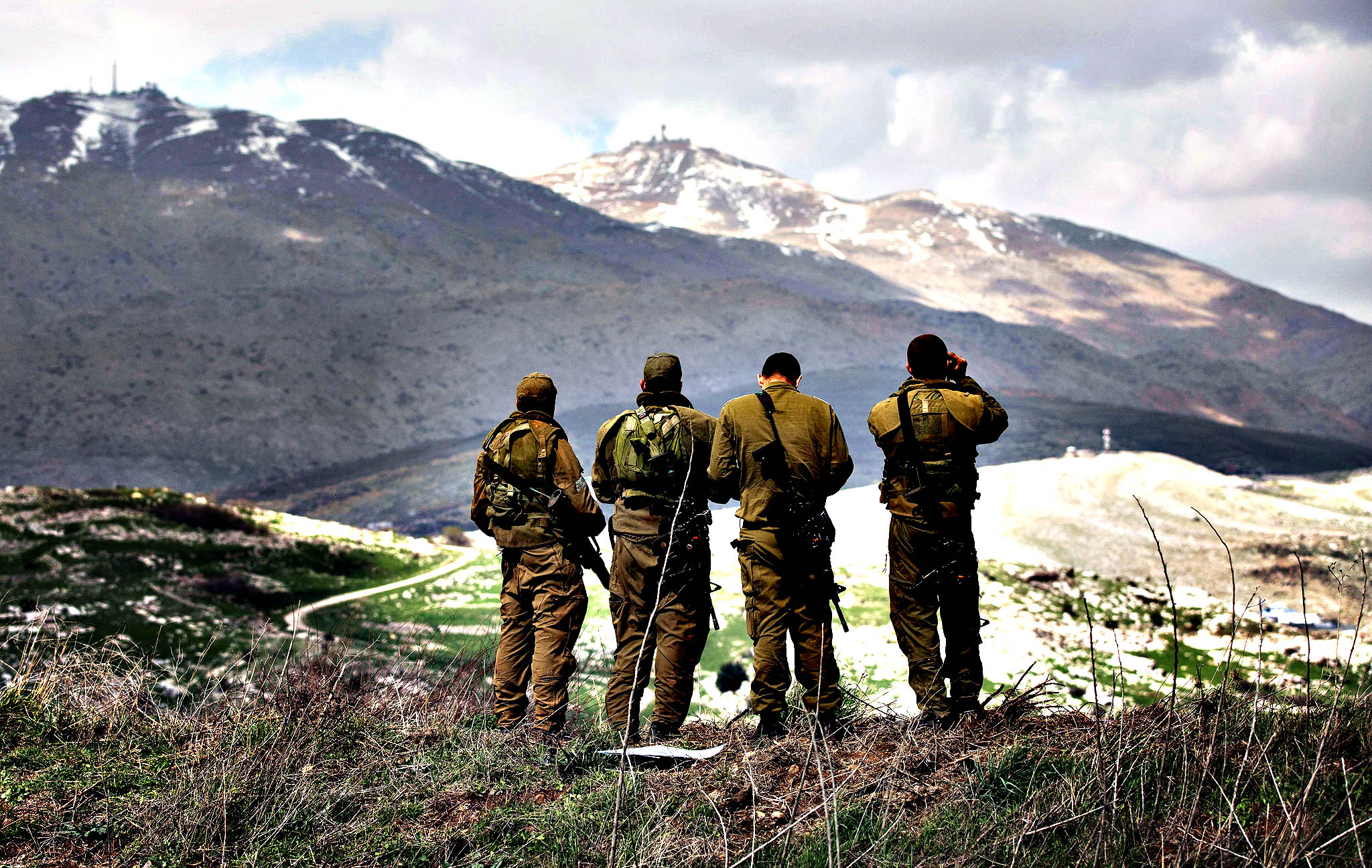 Israeli soldiers deployed on the border with Syria observe Syrian territory from Israeli side of the border near the Druze village of Majdal Shams on Wednesday in the Israeli-annexed Golan Heights. Israel launched air raids against Syrian army positions and issued a stark warning to Damascus just hours after a bomb on the occupied Golan Heights wounded four of its soldiers.
