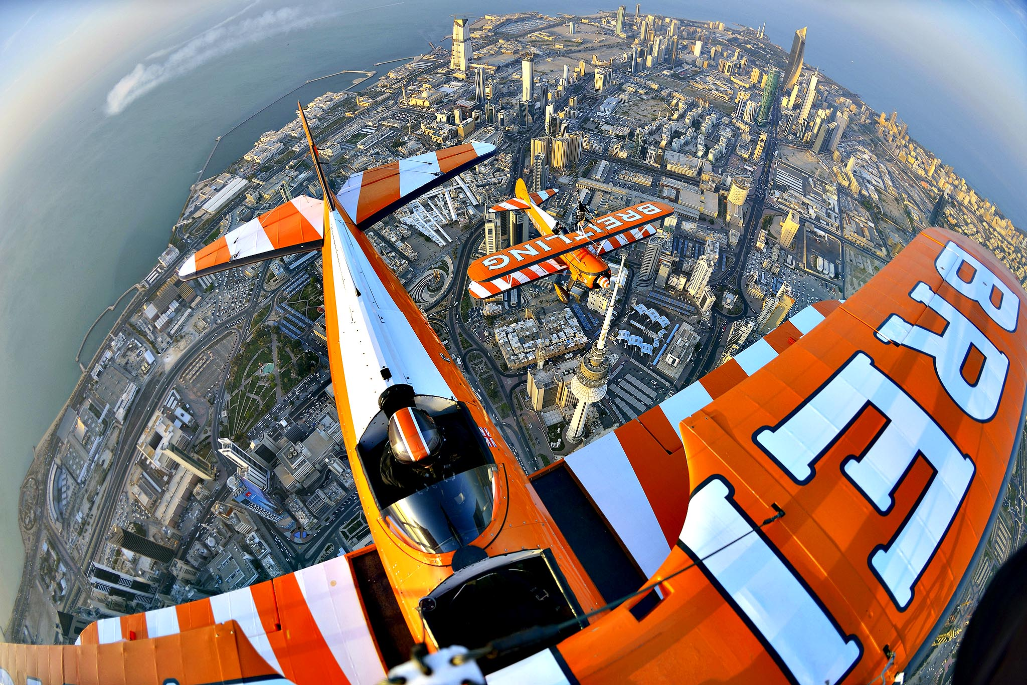 Breitling Wingwalker Freya Paterson, from Liverpool, UK, flies above Kuwait City's iconic Water Towers with pilots David Barrell and Martyn Carrington.  The team loop and roll up to 160 mph enduring G-forces of 4-5g. Crowds are expected to line the Kuwaiti coastline to catch a glimpse of the Wingwalking team on Saturday, to mark the opening of the first dedicated boutique in the city for the prestigious watch brand.