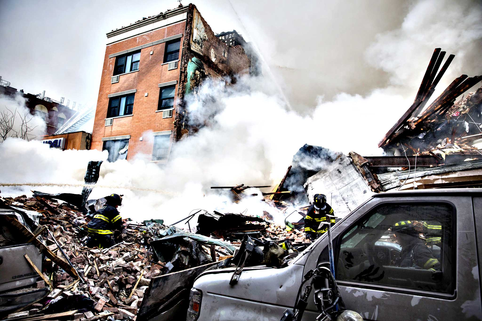 Heavy smoke pours from the debris as the Fire Department of New York (FDNY) responds to a 5-alarm fire and building collapse at 1646 Park Ave in the Harlem neighborhood of Manhattan March 12, 2014 in New York City. Reports of an explosion were heard before the collapse of two multiple-dwelling buildings that left at least 11 injured.