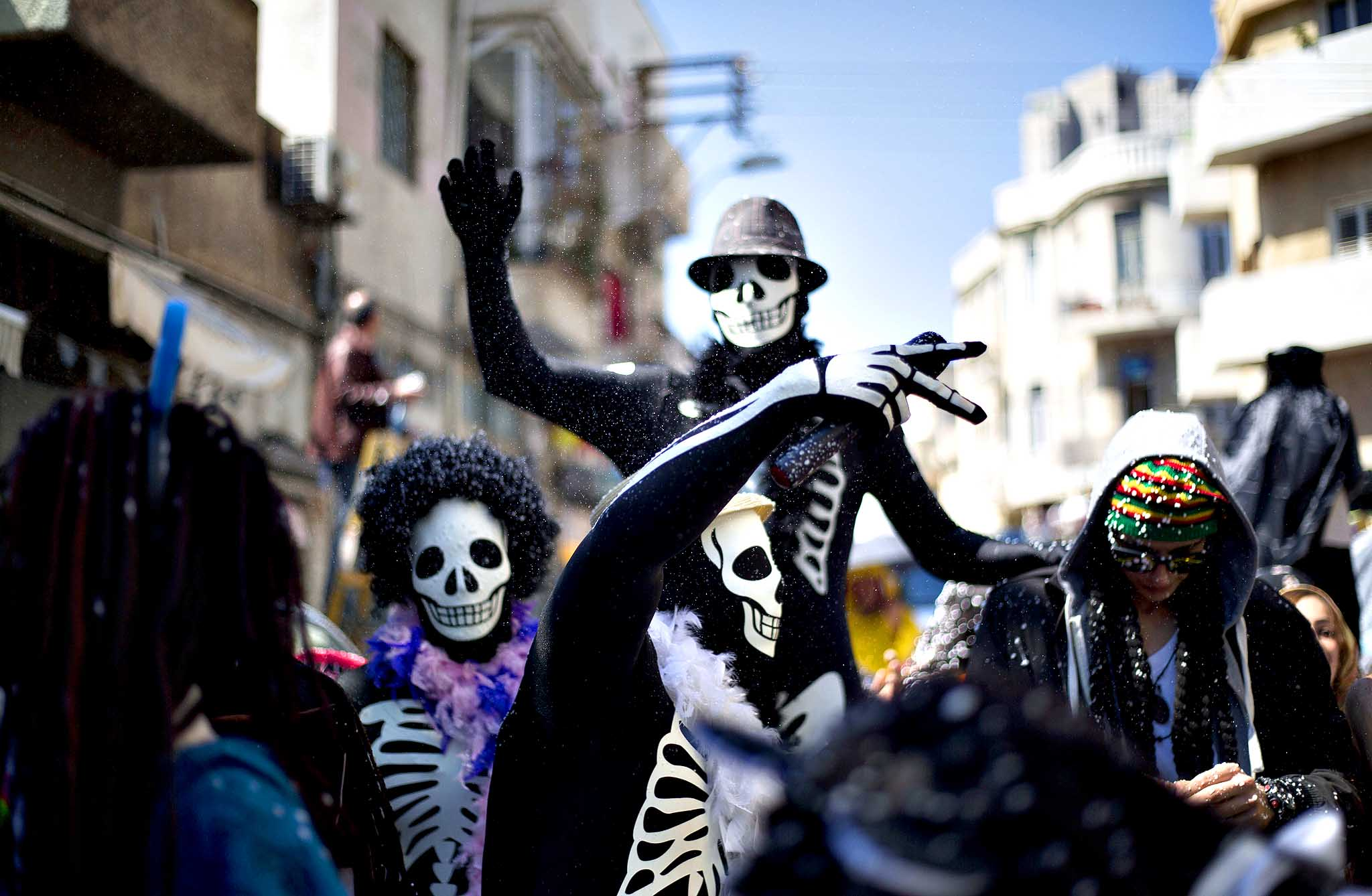 Young children of foreign migrant workers wear costumes as they march in a Purim parade in Tel Aviv, Israel, Friday, March 14, 2014. The Jewish holiday of Purim commemorates the Jews' salvation from genocide in ancient Persia, as recounted in the Book of Esther, which is read in synagogues. Other customs include: sending food parcels and giving charity; dressing up in masks and costumes; eating a festive meal; and public celebrations.
