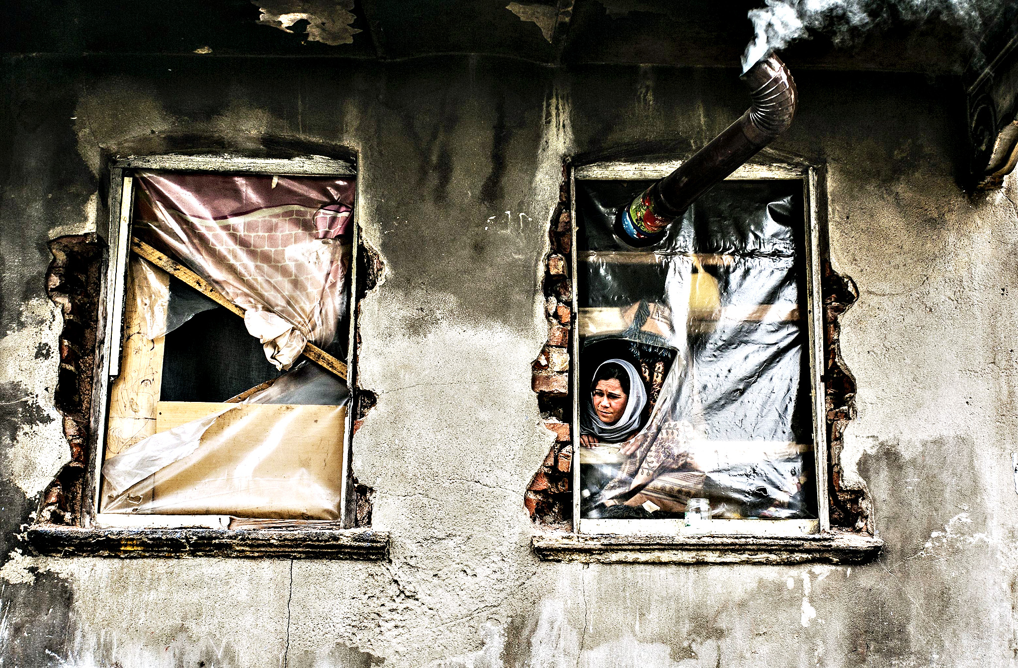 A Syrian refugee woman looks out from a window with no glass, in a house in the Kucukpazar area of Istanbul, on March  4, 2014. Syrian government forces are waging a campaign of siege warfare and starvation against civilians as part of its military strategy, a UN-mandated probe said on March 5. Syria's war has since March 2011 killed more than 140,000 people and forced millions more to flee.