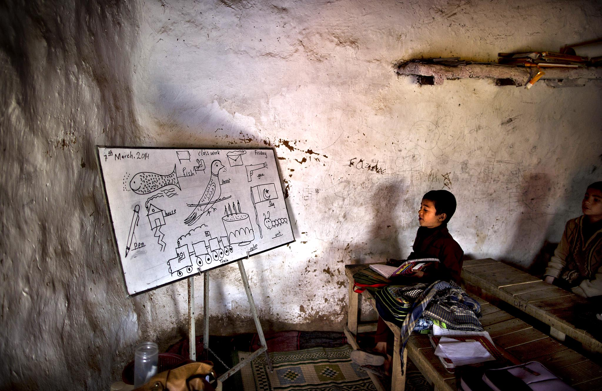 An Afghan refugee boy reads from the board while he and other schoolchildren attend their classes at their makeshift school on the outskirts of Islamabad, Pakistan, Friday, March 7, 2014.