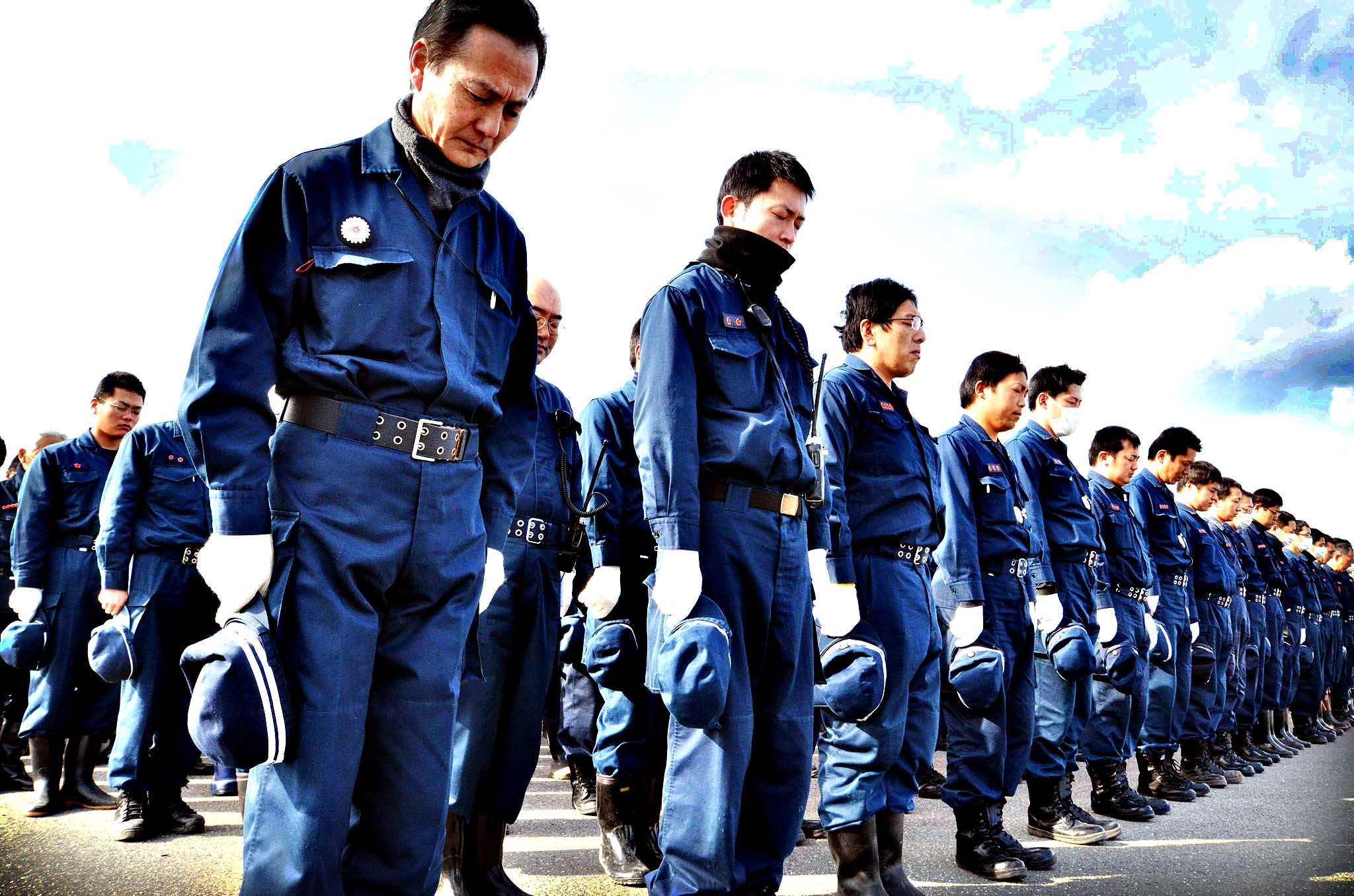 Police officers bow to offer prayers in silence for the victims in Namie, near the striken TEPCO Fukushima Dai-ichi nuclear plant in Fukushima prefecture on March 10, 2014, one day before the third anniversary of March 11 massive earthquake and tsunami.  The 9.0 magnitude earthquake in 2011 sent a huge wall of water into the coast of the Tohoku region, splintering whole communities, ruining swathes of prime farmland and killing nearly 19,000 people.