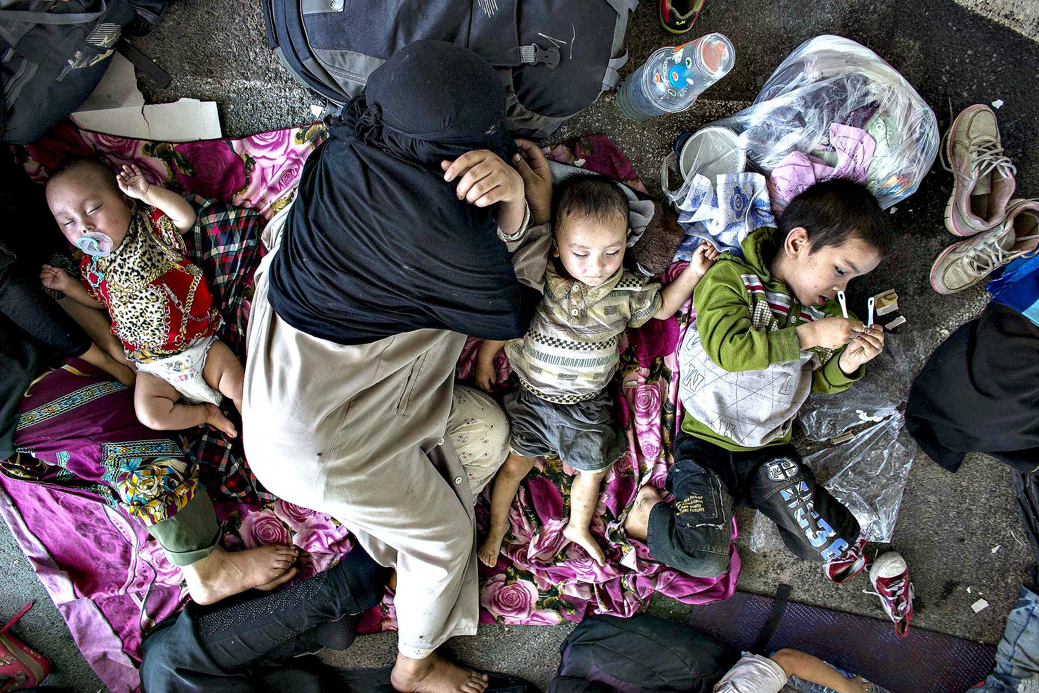 Suspected Uighurs from China's region of Xinjiang, rest inside a temporary shelter after they were detained at the immigration regional headquarters near Thailand-Malaysia border in Hatyai...Suspected Uighurs from China's troubled far-western region of Xinjiang, rest inside a temporary shelter after they were detained at the immigration regional headquarters near Thailand-Malaysia border in Hatyai, Songkla March 14, 2014. About 200 people rescued by police from a human smuggling camp in southern Thailand on Wednesday are suspected Uighur Muslims from China's troubled far-western region of Xinjiang, say Thai police.