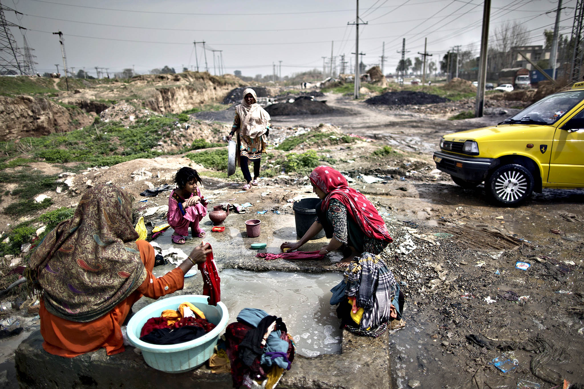 Pakistani women, wash their laundry at a water reservoir, on the outskirts of Islamabad, Pakistan, Thursday, March 20, 2014. The United Nations has proclaimed that March 20 is the International Day of Happiness.