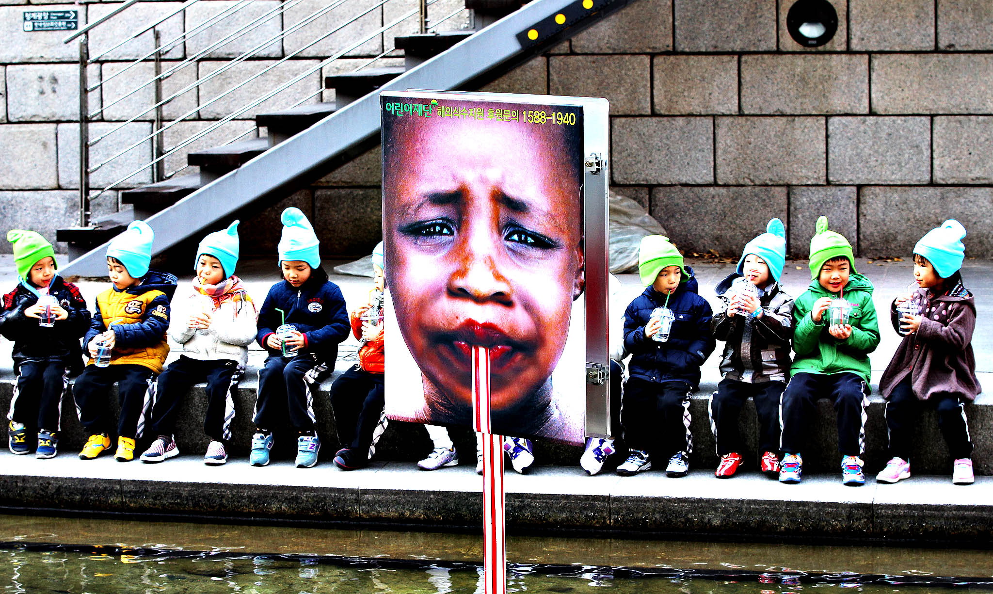Kindergartners drink waters near a poster to mark the World Water Day, which falls on March 22, on Cheonggye Stream in Seoul, South Korea, Thursday, March 20, 2014.