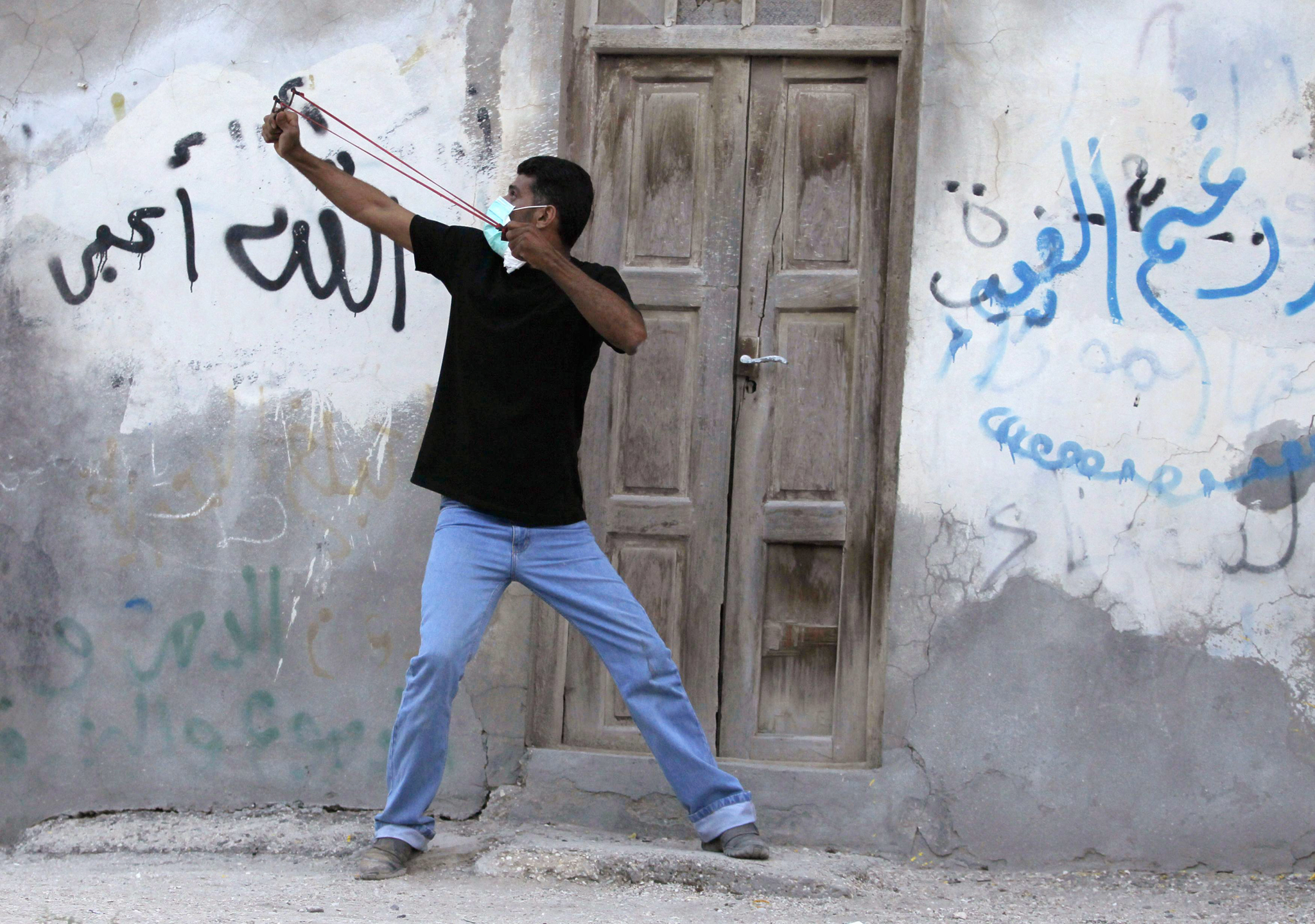 An anti-government protester takes aim at riot police with his slingshot during clashes after the funeral procession of Ali Abbas and Ahmed Al Mesjen who died when their car exploded in the village of Maqsha west of Manama...An anti-government protester takes aim at riot police with his slingshot during clashes after the funeral procession of Ali Abbas and Ahmed Al Mesjen who died when their car exploded in the village of Maqsha west of Manama, April 22, 2014. REUTERS/Hamad I Mohammed (BAHRAIN - T