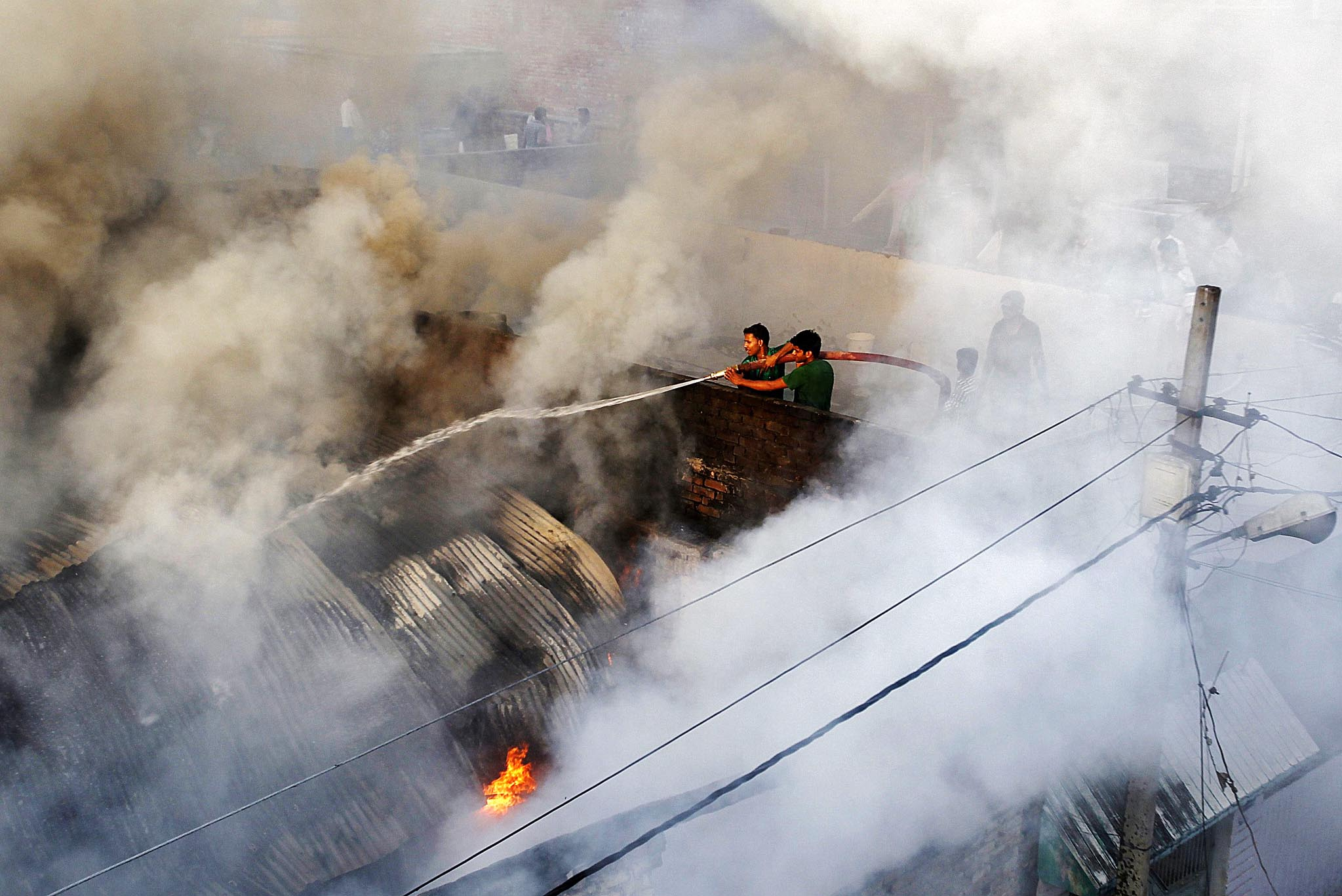 Firefighters try to douse a fire at a cotton factory in Allahabad