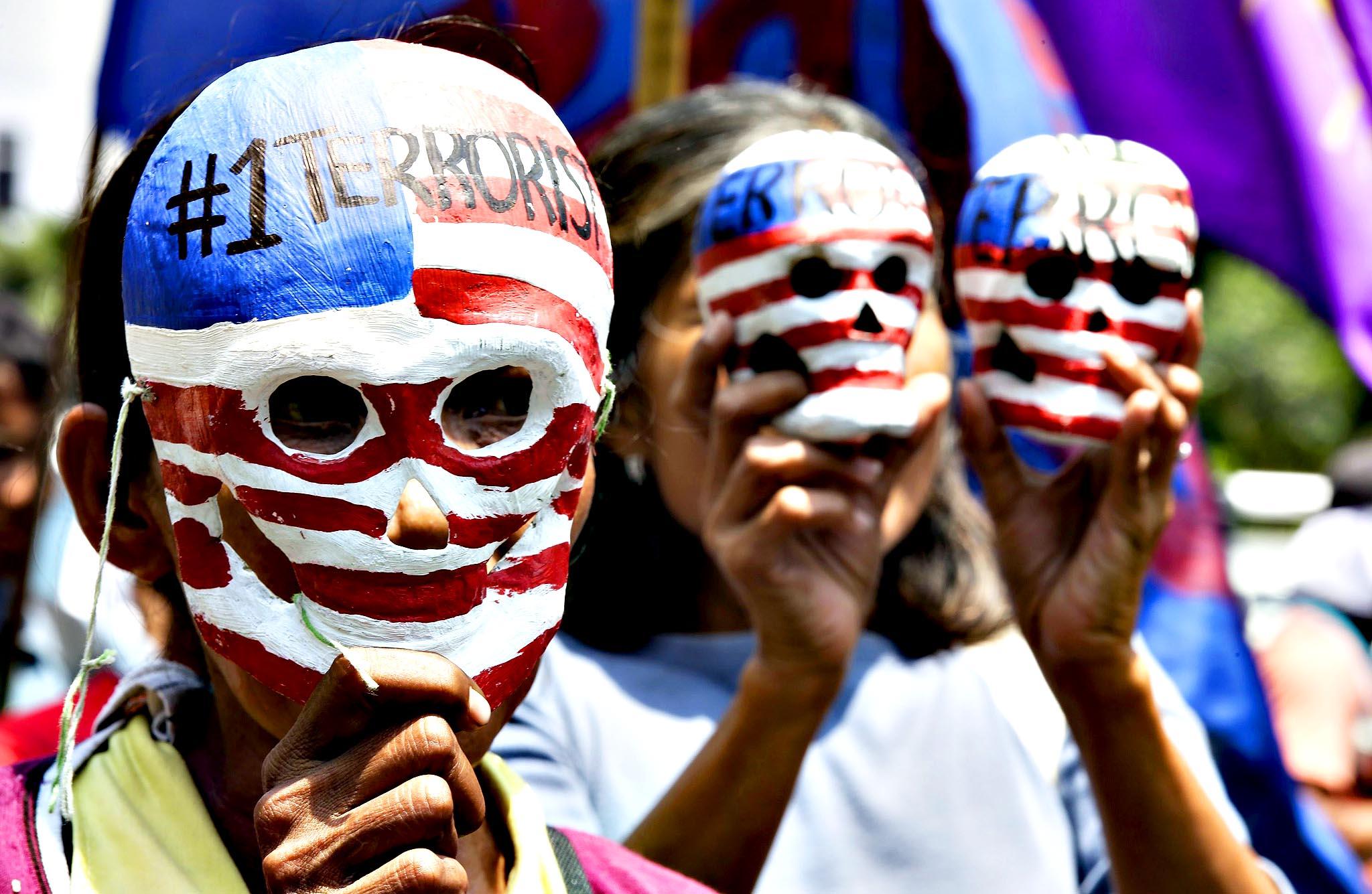 Filipino activists hold paper mache skulls  painted with US flags as they march outside the US embassy in Manila, Philippines on Monday in a rally condemning the upcoming visit of US President Barack Obama to the country. Activists also called for an end to the presence of US troops in the country and the Visiting Forces Agreement (VFA).