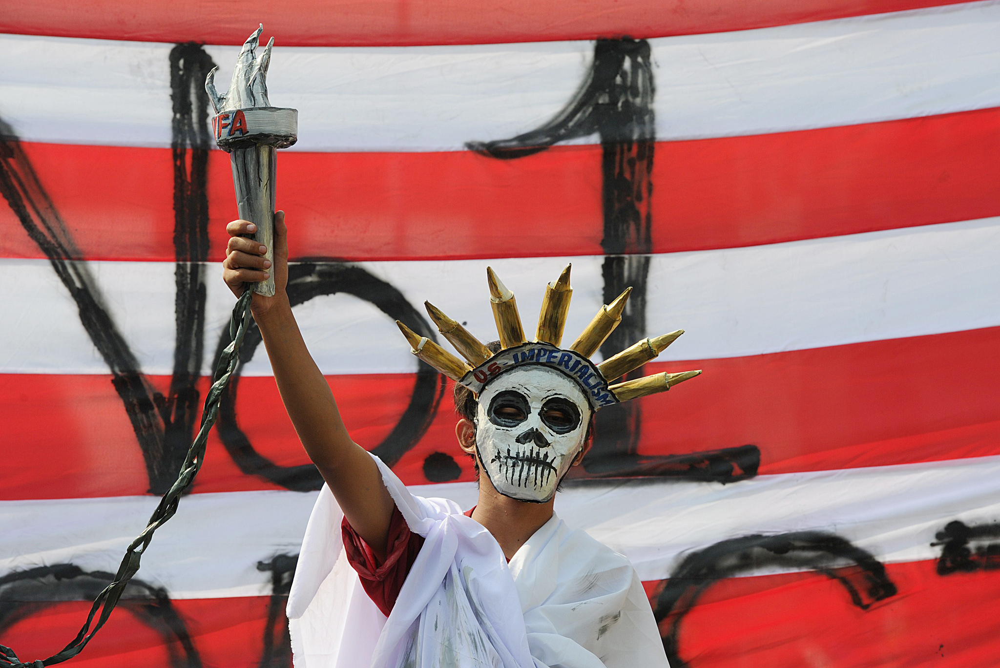 "An anti-US protester dressed like the St...An anti-US protester dressed like the Statue of Liberty stands next to a giant mock US flag during a protest near the Malacanang palace in Manila on April 29, 2014, as US President Barack Obama's visit to the capital winds down. The protesters were protesting against the newly-signed defense agreement between the US and the Philippines, with President Obama ending an Asian tour April 29 with a warning to China against using force to resolve territorial disputes, and an ""ironclad"" promise of military support for the Philippines.     AFP PHOTO/TED ALJIBETED ALJIBE/AFP/Getty Images"