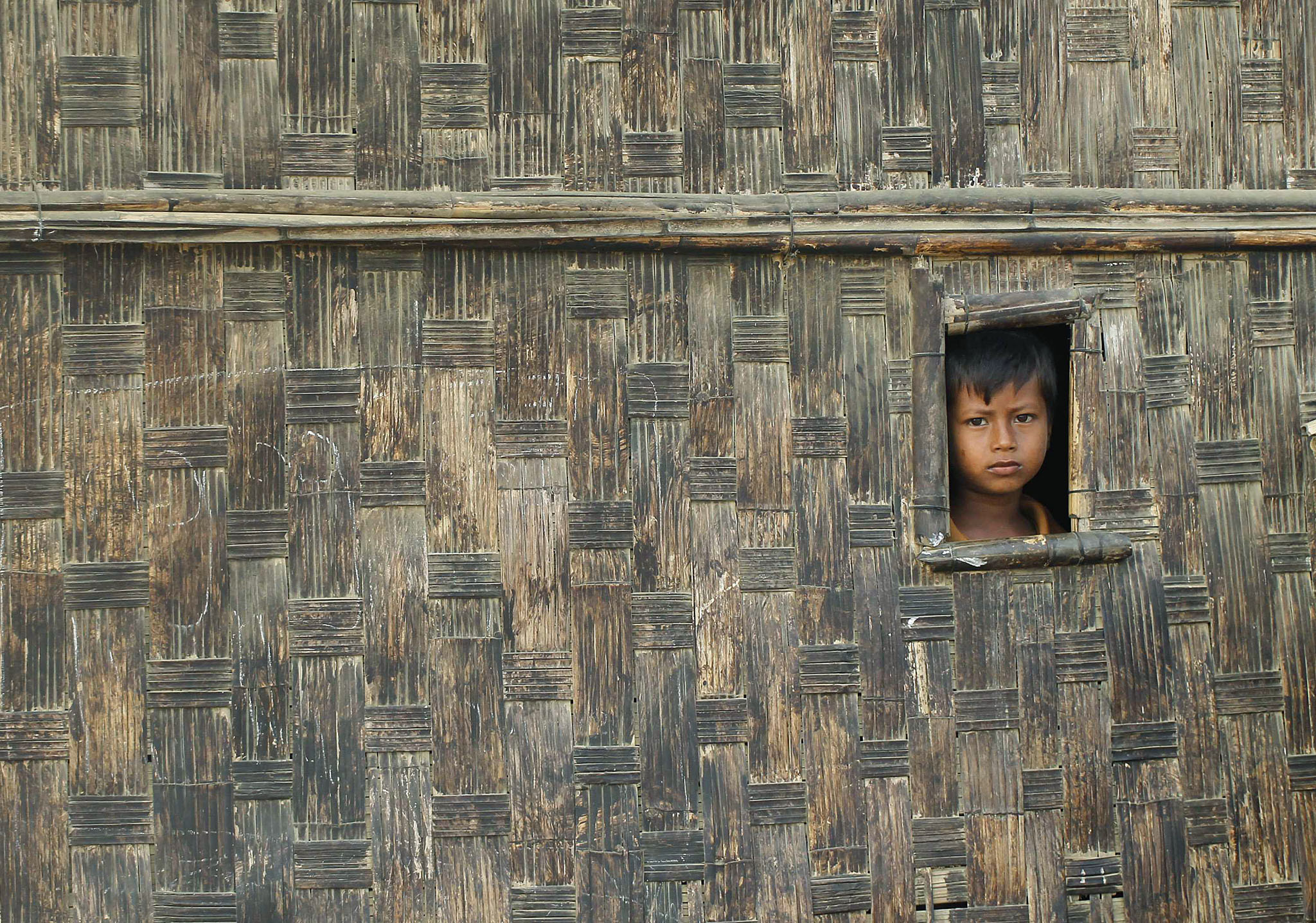 A boy looks from his temporary shelter at a Rohingya refugee camp as Myanmar's government embarks on a national census, in Sittwe April 2, 2014. At least 20,000 people in displacement camps around Sittwe will run out of drinking water within 10 days, while food stocks will run out within two weeks, imperilling thousands more. In the absence of nongovernment organisations (NGOs), the United Nations is working with the government to bring emergency supplies to camps, but that is only a short-term solution, said Pierre Peron, a spokesman for the UN Office for the Coordination of Humanitarian Affairs. The evacuation of aid workers came as Myanmar prepared to launch its first census since 1983, which sparked controversy because it included questions on religion and ethnicity. Those are sensitive subjects in a country riven by sectarian tensions and especially in Rakhine, which is home to a million mostly stateless Rohingya whom the government refers to as Bengali, implying they are illegal immigrants from Bangladesh