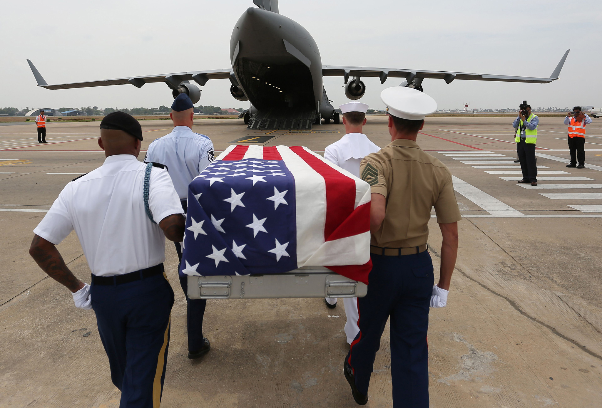 US soldiers carry a flag-draped coffin containing the remains believed to be of a US soldier during a repatriation ceremony at Phnom Penh International Airport.  Remains believed to be those of three US servicemen killed in Cambodia more than four decades ago during the Vietnam War were repatriated for identification in the United States