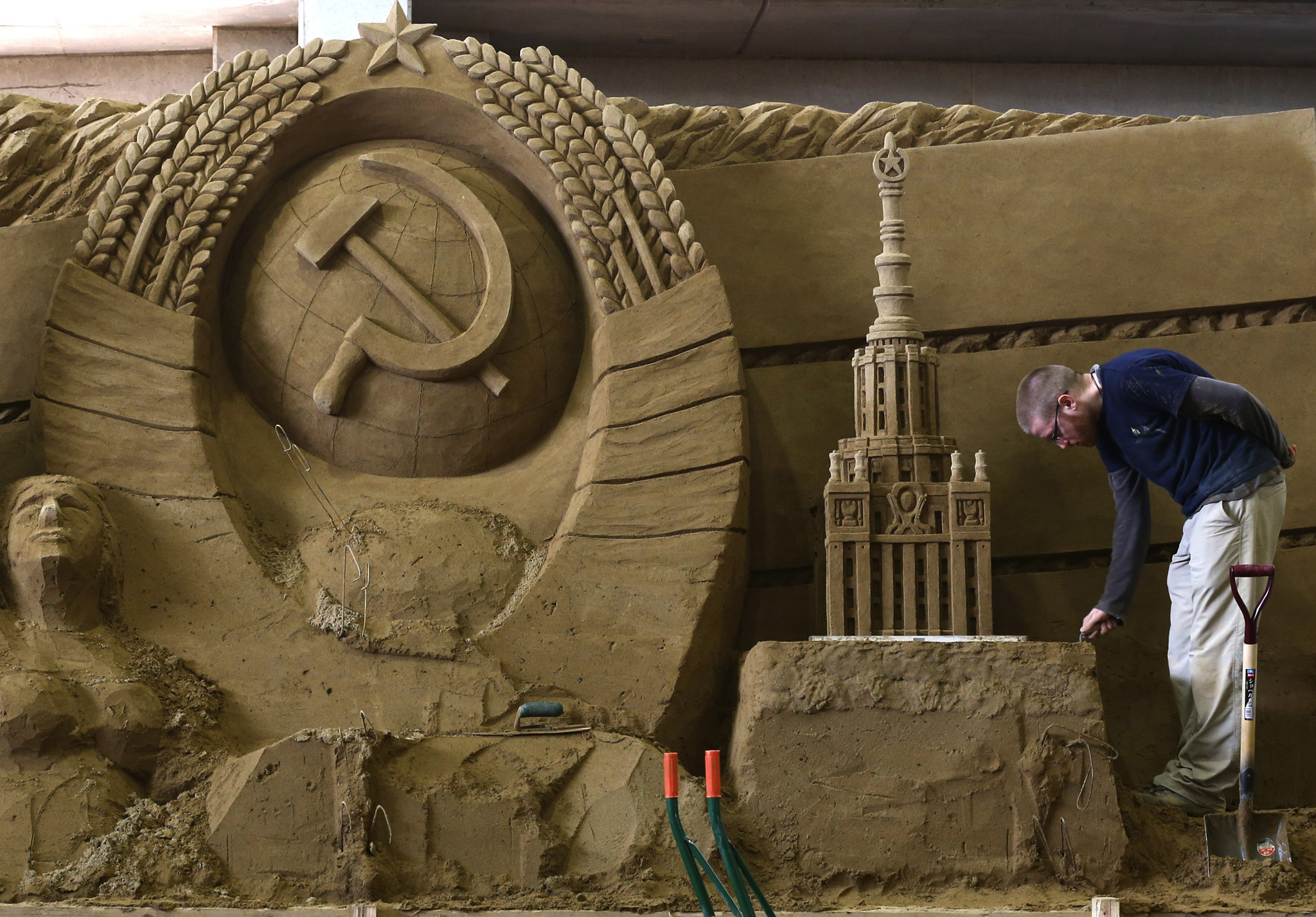 "Guy Deveau of Canada finishes a sand sculpture named ""Soviet Union"" at the Sand Museum in the Tottori Dune in Tottori, Japan. The 7th annual sand sculpture exhibition hosted by this world's first sand museum, features the theme ""Russia"" this year as mark to hosted 2014 Winter Olympic Game in Sochi. The exhibition is open to the public from April 19, 2014 to January 4, 2015"