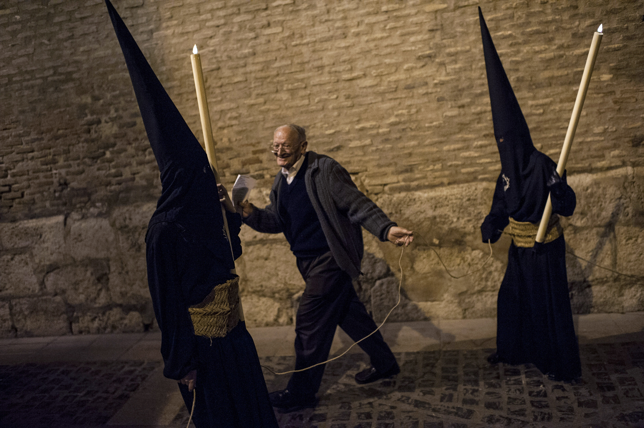 "A man crosses between two masked penitents as they take part in the procession of the ""Silencio del Santisimo Cristo del Rebate"" brotherhood, during Holy Week in Tarazona, northern Spain, Tuesday, April 15, 2014. Hundreds of processions take place throughout Spain during the Easter Holy Week. (AP Photo/Alvaro Barrientos)"