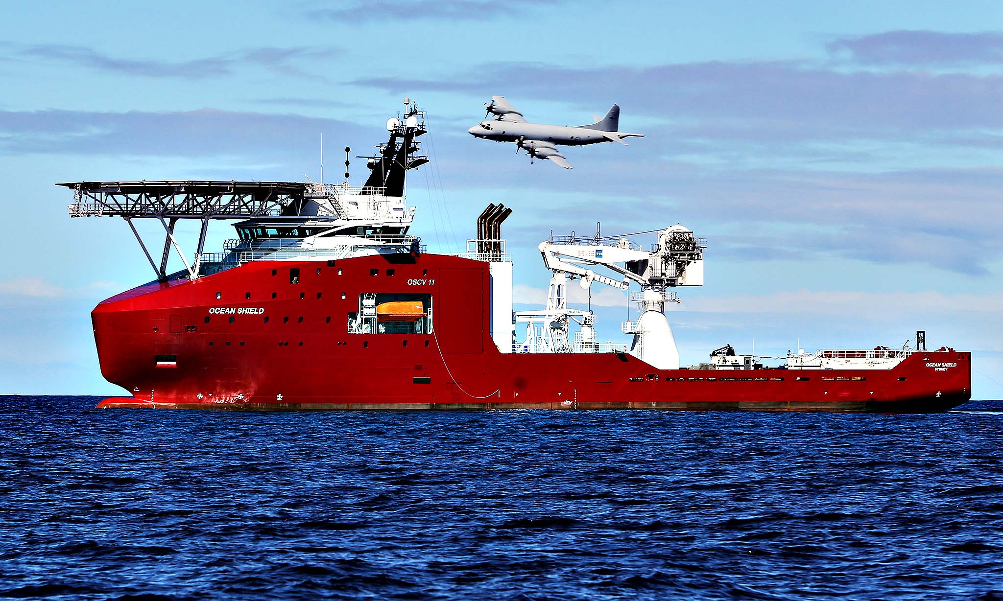In this April 9, 2014 photo provided by the Australian Defense Force, a Royal Australian Air Force AP-3C Orion flies past Australian Defense vessel Ocean Shield on a mission to drop sonar buoys to assist in the acoustic search of the missing Malaysia Airlines Flight 370 in the southern Indian Ocean. The ship searching for the missing Malaysian jet has detected two more underwater signals that may be emanating from the aircraft's black boxes, and the Australian official in charge of the search expressed hope Wednesday that the plane's wreckage will soon be found.