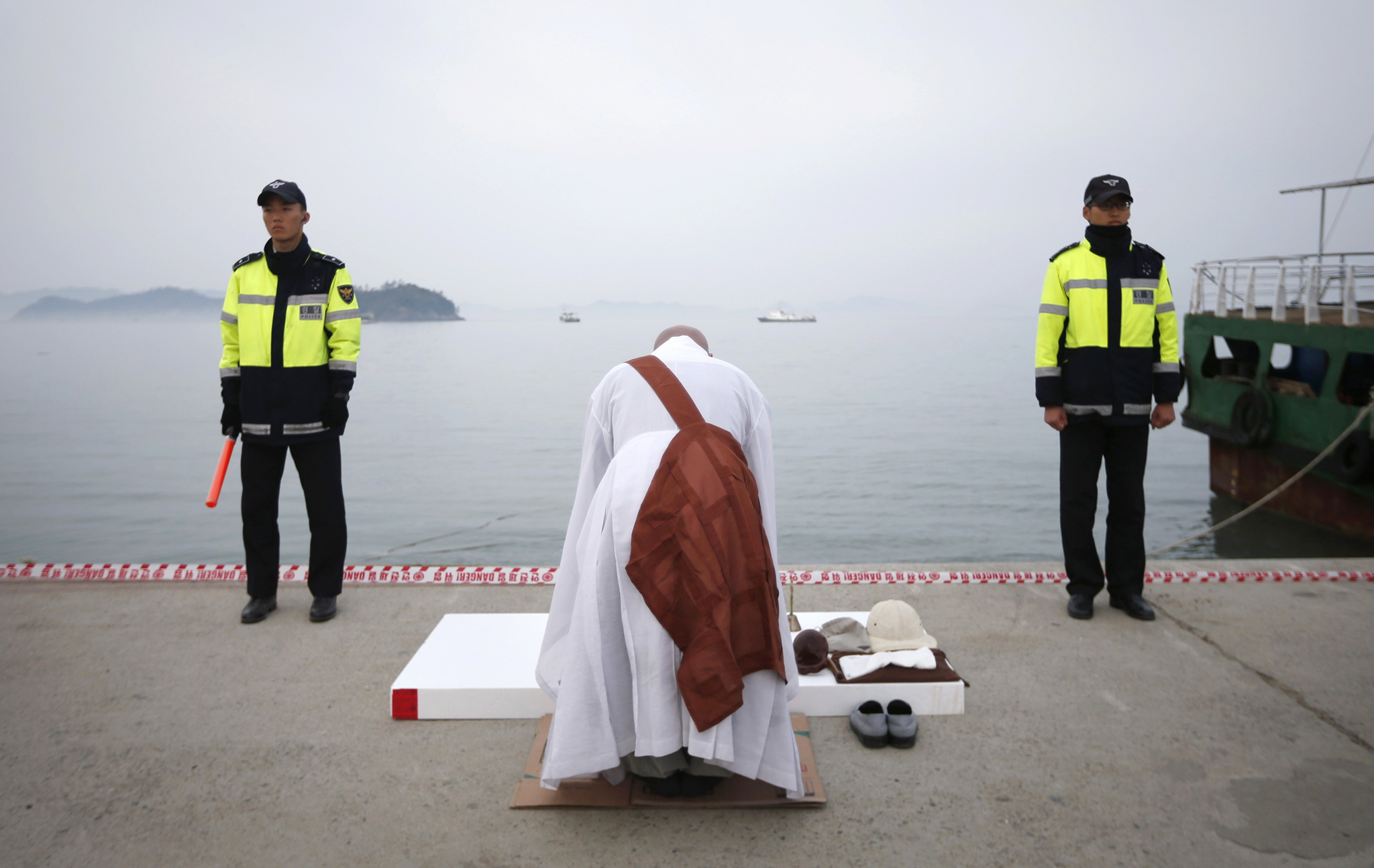 Two policemen stand guard as a priest says prayers at the port in Jindo, where family members are waiting for bodies recovered from the capsized passenger ship Sewol April 22, 2014. The crew of the South Korean ferry that sank with hundreds of people on board repeatedly asked officers on the bridge whether or not to give the order to abandon ship, but there was no response, a crew member has said. The Sewol ferry sank last Wednesday on a routine trip south from the port of Incheon to the sub-tropical holiday island of Jeju. REUTERS/Kim Hong-Ji