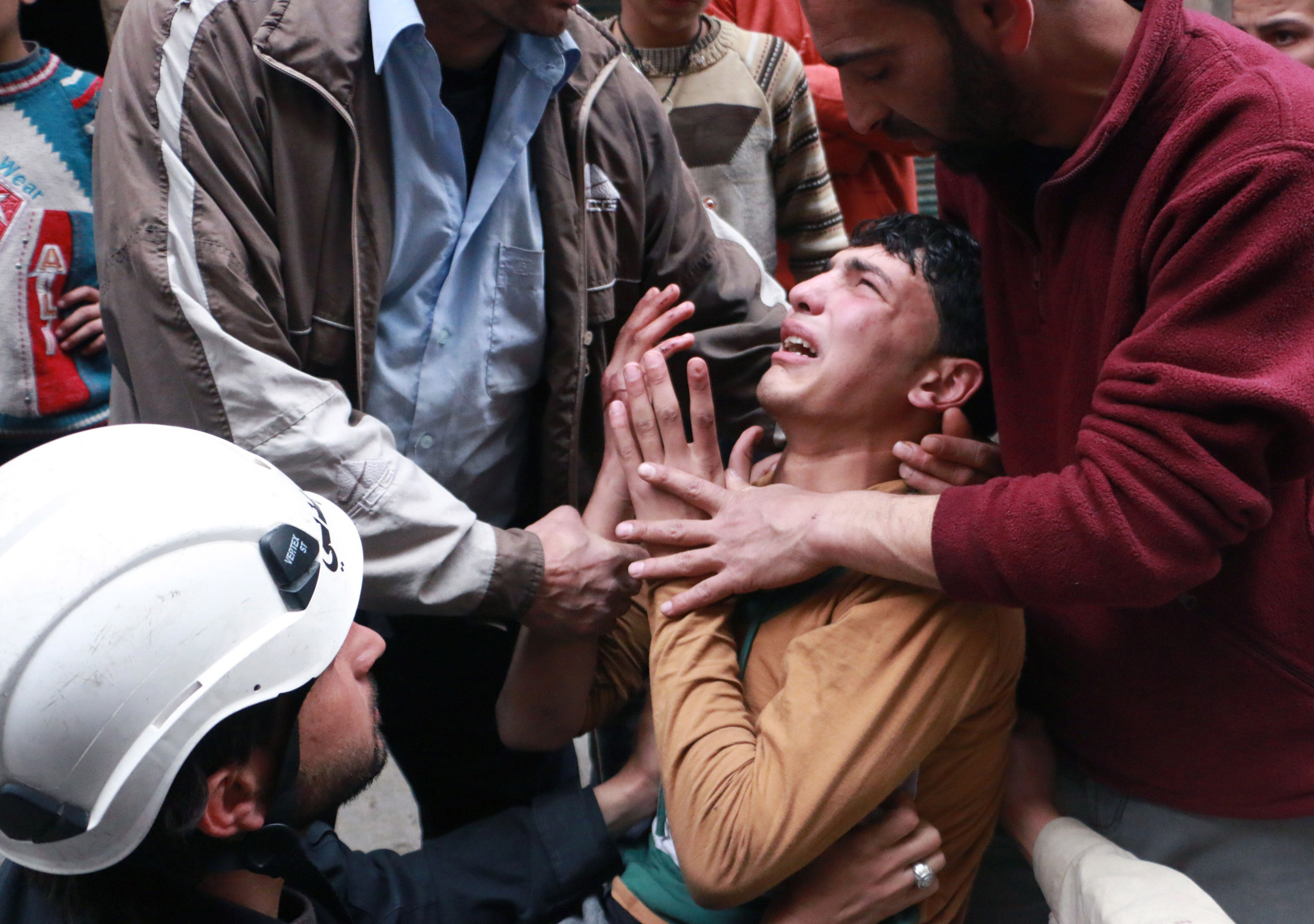 TOPSHOTS A man is comforted by a rescue ...TOPSHOTS A man is comforted by a rescue worker and others following a reported air strike by government forces in which a fellow rescue worker was killed on March 8, 2014 in the northern city of Aleppo. More than 140,000 people have been killed in Syria since the start of a March 2011 uprising against the Assad family's 40-year rule. AFP PHOTO / AMC / FADI AL-HALABIFadi al-Halabi/AFP/Getty Images