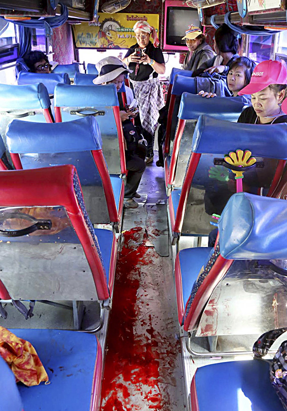 Anti-government protesters look at bloodstained floor of the bus they were traveling after an attack by suspected gunmen while on their way back from a protest in Bangkok, Thailand Tuesday, April 1, 2014. Gunmen have fired on a convoy of anti-government protesters in Thailand's capital, and four people have been wounded. (AP Photo)