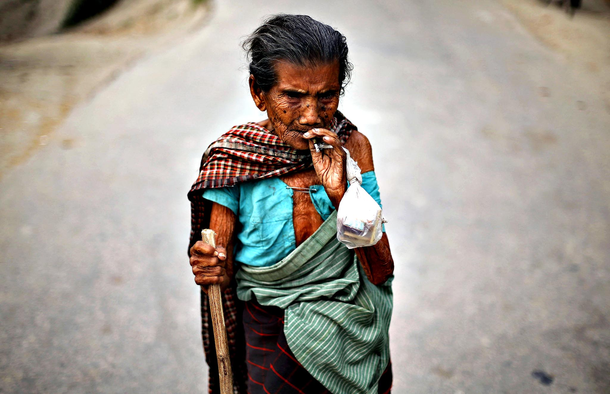 A woman smokes bidi, a local cigarette hand-rolled with tobacco leaf, as she arrives to cast her vote, outside a polling station in Majuli, a large river island in the Brahmaputra river, Jorhat district, in the northeastern Indian state of Assam April 7, 2014. The first electors cast their votes in the world's biggest election on Monday with Hindu nationalist opposition candidate Narendra Modi seen holding a strong lead on promises of economic revival and jobs but likely to fall short of a majority.