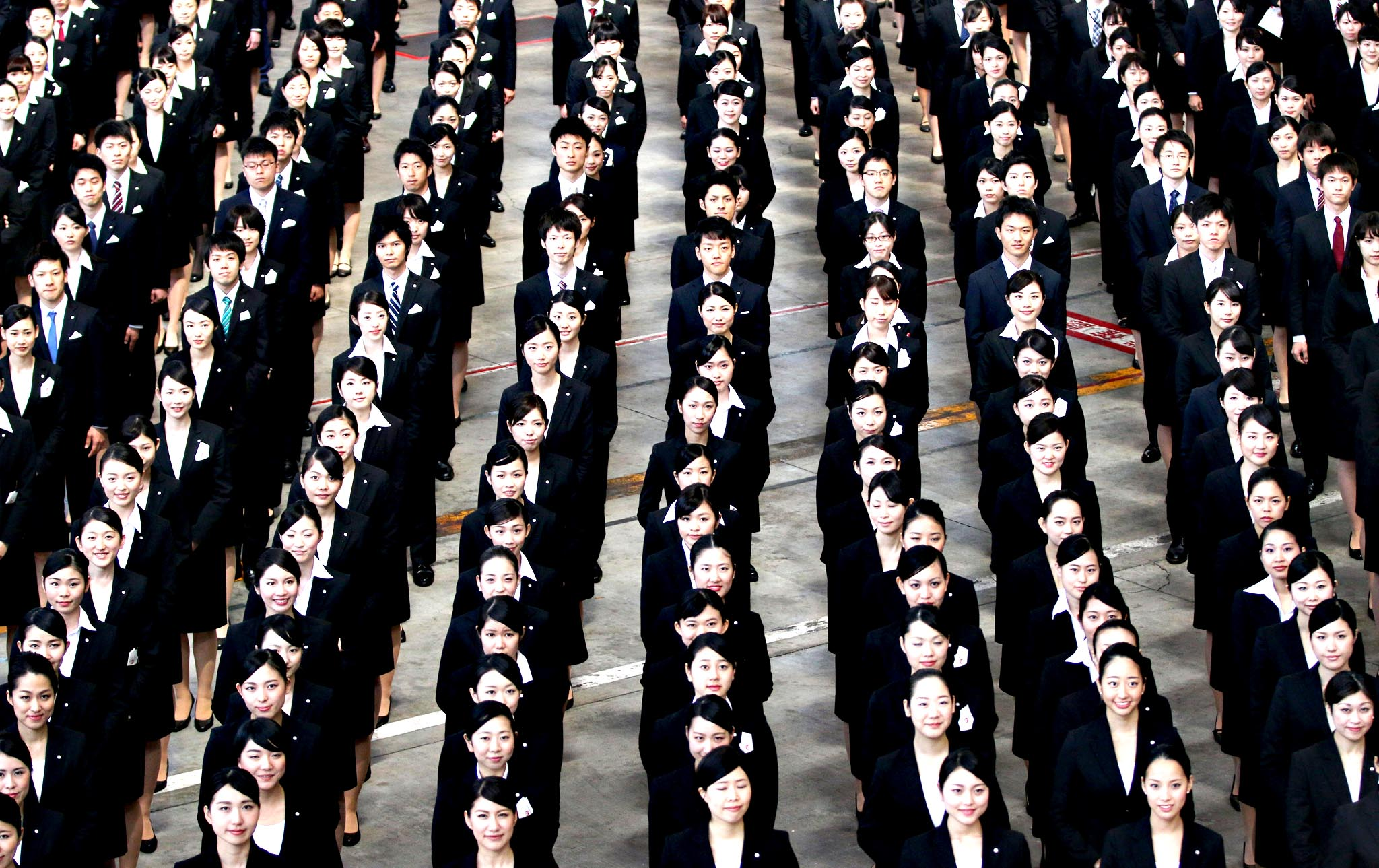 Japan Airlines Co. (JAL) group companies' new employees line up for a photograph during a welcoming ceremony at the company's hangar near Haneda Airport in Tokyo, Japan, on Tuesday, April 1, 2014. The jobless rate dropped to 3.6% in the world s third-largest economy according to data released on March 28.