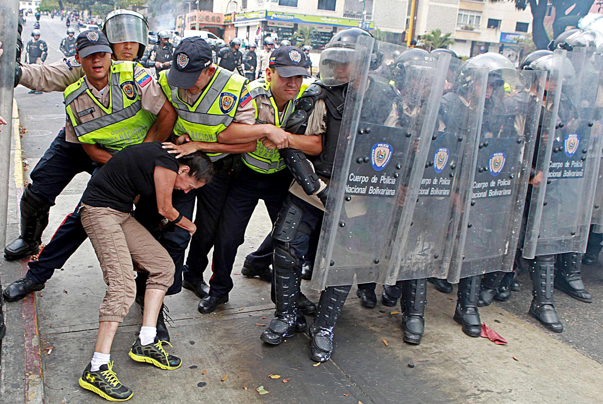 An anti-government activist clashes with riot police
