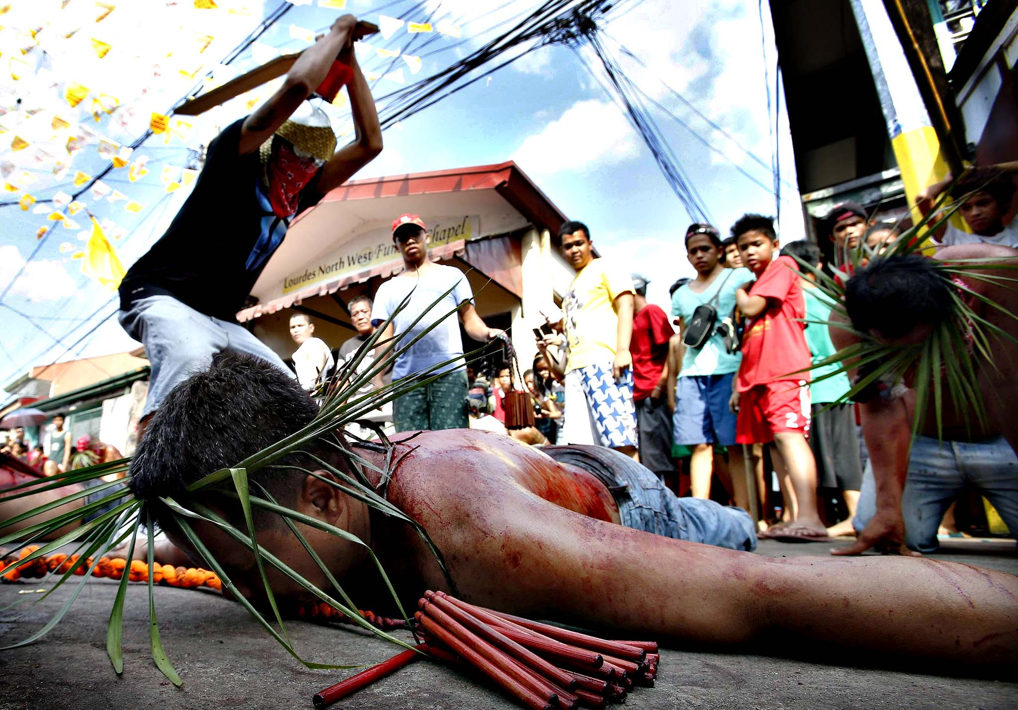 Man whips a devotee during a Maundy Thursday ritual by penitents to atone for sins in Angeles...A man whips a devotee during a Maundy Thursday ritual by penitents to atone for sins in Angeles, Pampanga north of Manila April 17, 2014. Flagellation is a form of religious discipline observed every lenten season by Catholic devotees in the Philippines