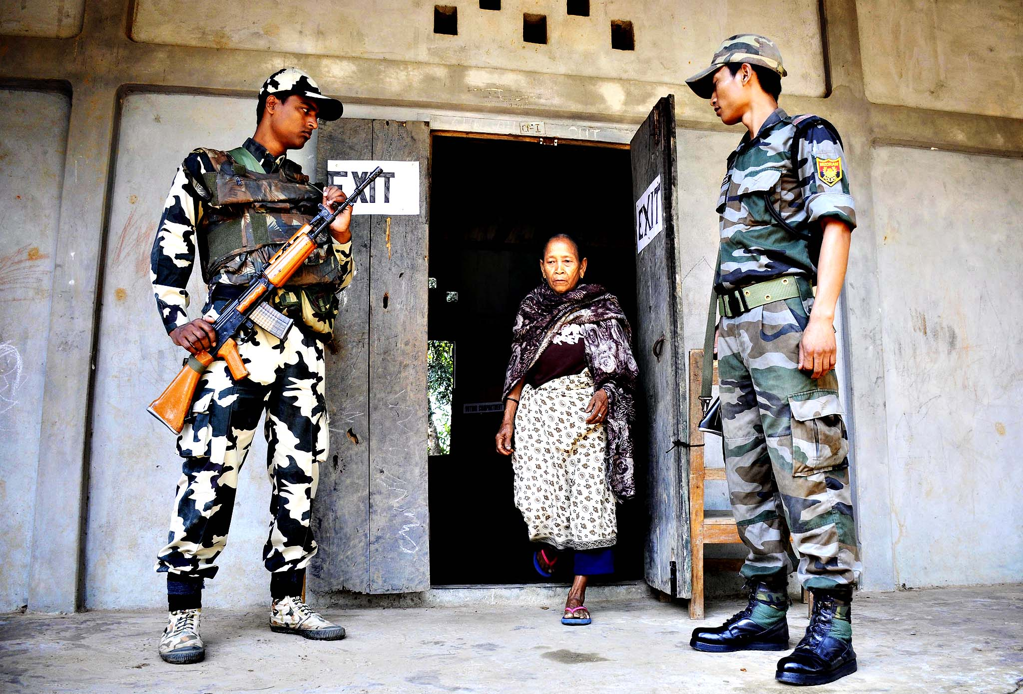 Indian security personnel look on as a voter leaves a polling station after casting her ballot in Kahnmun, some 190 kms from Aizwal, the capital of the northeastern Indian state of Mizoram on April 11, 2014. Indians began voting April 7 in the world's biggest election, which is set to sweep the Hindu nationalist opposition to power at a time of low growth, anger over corruption and warnings about religious unrest. Elections are being held in nine phases from April 7 until May 12.