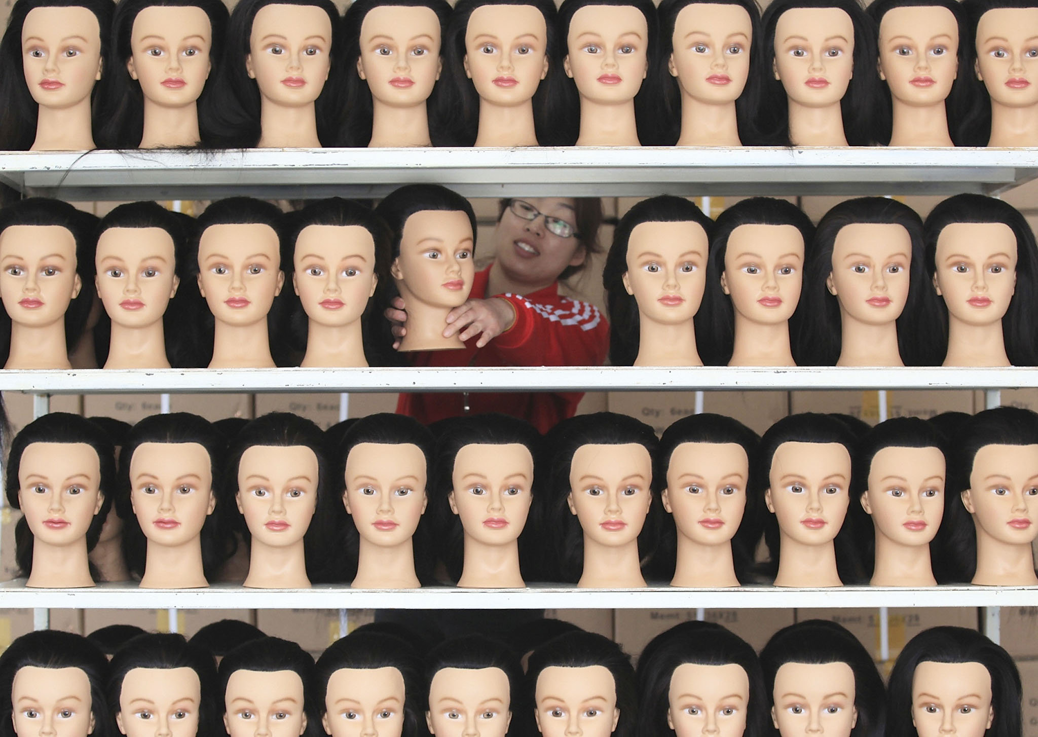 Home at theIn this Tuesday, April 1, 2014 photo, a woman lines up mannequin heads on a shelf at a company making fashion wigs for export in Jimo city in east China's Shandong province. Growth in the developing economies of Asia will edge higher as the recovery in rich countries helps the region weather the slowdown in China, the Asian Development Bank said Tuesday.