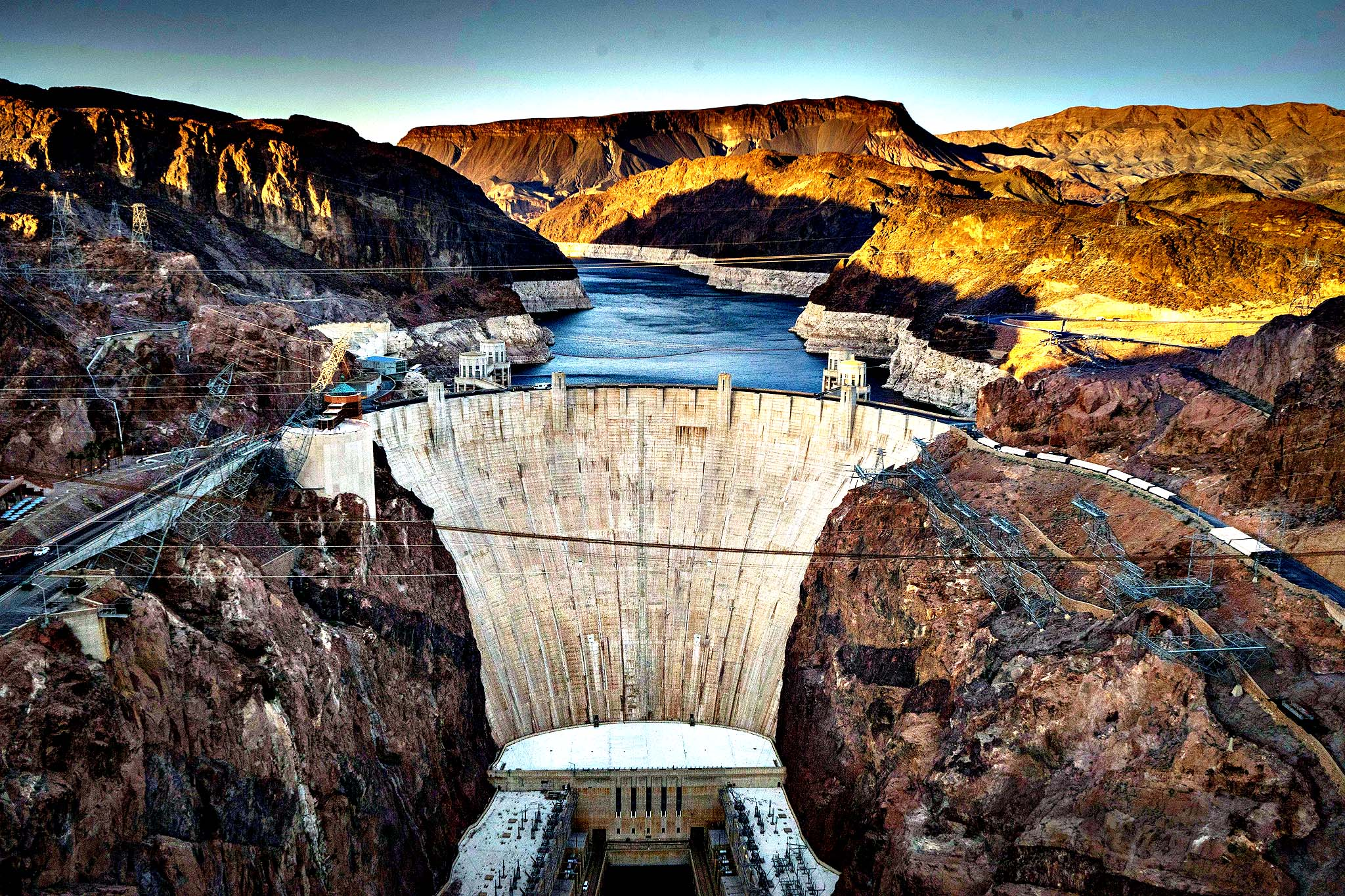 Hoover Dam, a concrete arch-gravity dam in the Black Canyon of the Colorado River on the border between the US states of Arizona and Nevada. Hoover Dam ,finished in 1936, impounds Lake Mead, the largest reservoir in the United States by volume. The dam's generators provide power for public and private utilities in Nevada, Arizona, and California. Hoover Dam is a major tourist attraction; nearly a million people tour the dam each year.