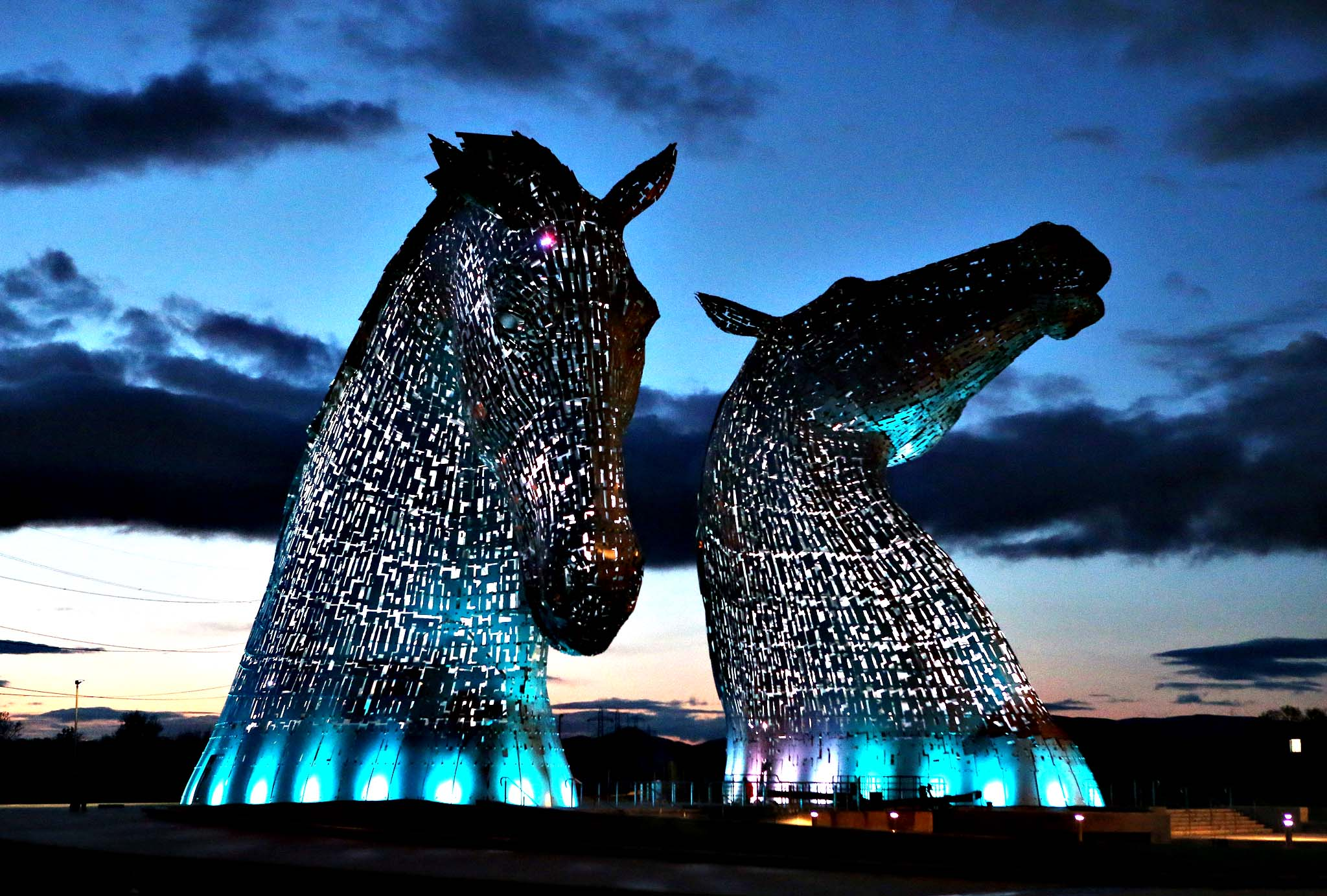 A lighting test is carried out on the Kelpies in Falkirk ahead of their  official opening to the public later this month. Designed by sculptor Andy Scott each of The Kelpies stands up to 30 metres tall and each one weighs over 300 tonnes. They are constructed of structural steel with a stainless steel outer skin, they pay homage to the tradition of working horses of Scotland which used to pull barges along Scotland's canals.  They stand at the entrance to the North Sea at the Forth and Clyde canal.