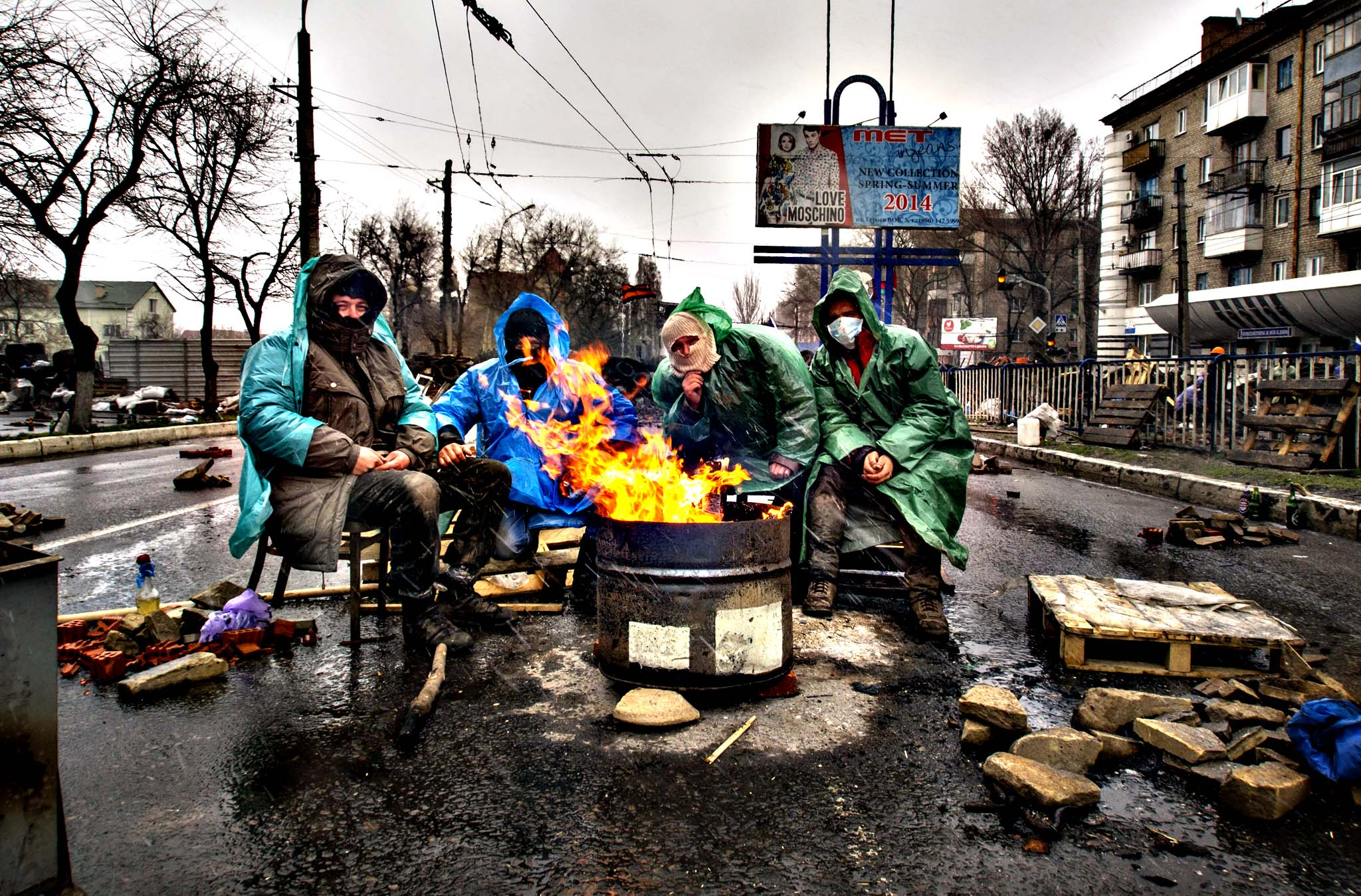 Pro-Russian activists warm themselves at a bonfire next to barricades in front of an entrance to the Ukrainian regional office of the Security Service in Luhansk, 30 kilometers (20 miles) west of the Russian border, in Ukraine, Friday, April 11, 2014. Ukraine s prime minister Arseniy Yatsenyuk on Friday told leaders in the country s restive east that he is committed to allowing regions to have more powers. Yatsenyuk told the meeting, which did not include representatives of the separatists, that more authority should be delegated to regional authorities.
