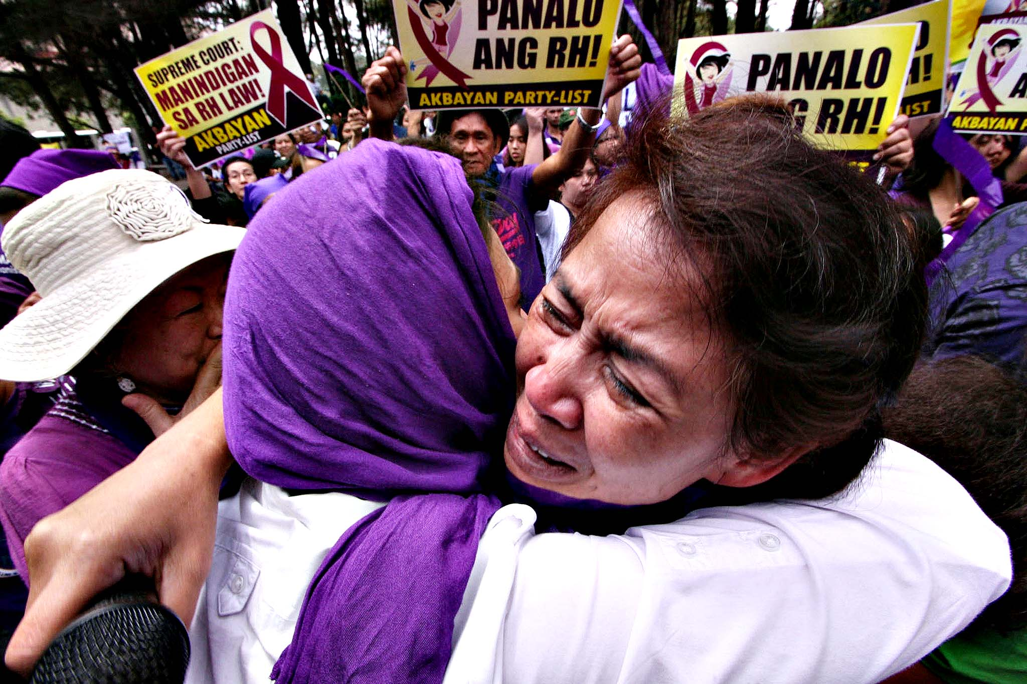 Supporters of the controversial birth control or Reproductive Health (RH) law celebrate in front of the court's summer residence in Baguio City, Trinidad province, north of Manila on April 8, 2014, after the Philippine supreme court declared it as not unconstitutional. The Philippines' highest court approved on April 8, a controversial birth control law that supporters said would transform the lives of millions of poor Filipinos, in a stunning defeat for the powerful Catholic Church.